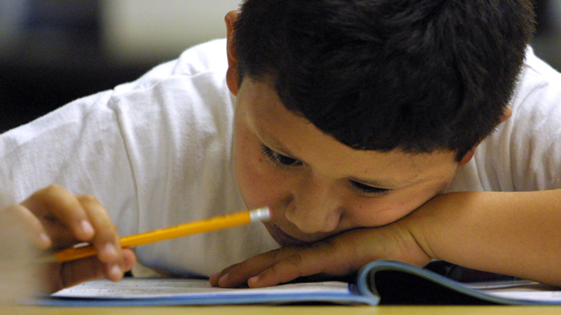 A young student in a second grade bilingual class looks closely at a math exam. (Photo by Tim Boyle/Getty Images)