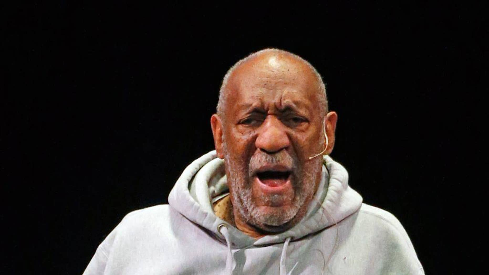 FILE - In this Jan. 17, 2015 file photo, comedian Bill Cosby performs at the Buell Theater in Denver. Cosby's stand-up tour is making a stop in northern Ohio, where police say they will have extra officers on hand for the show. Police in Sandusky expect at least a few protesters outside the theater where Cosby will perform Friday night. The 77-year-old comedian is facing sexual assault accusations from at least 15 women, with some of the claims dating back decades. He has denied the allegations through his attorney and has never been charged with a crime. (AP Photo/Brennan Linsley, File)