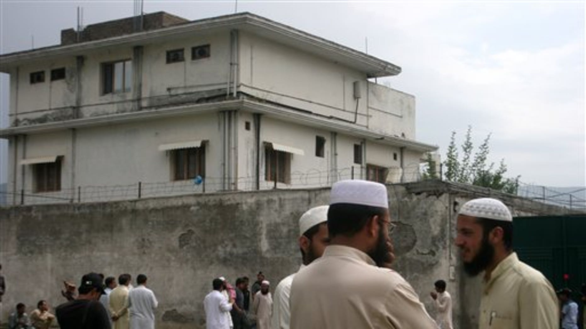 In this May 5, 2011 file photo, local residents and media are seen outside the house where Al Qaeda leader Usama bin Laden was caught and killed in Abbottabad, Pakistan. The courier who led U.S. intelligence to bin Laden's hideout in Pakistan hailed from the Swat Valley, a one-time stronghold of militant Taliban fighters, Pakistani officials said. (AP/File)