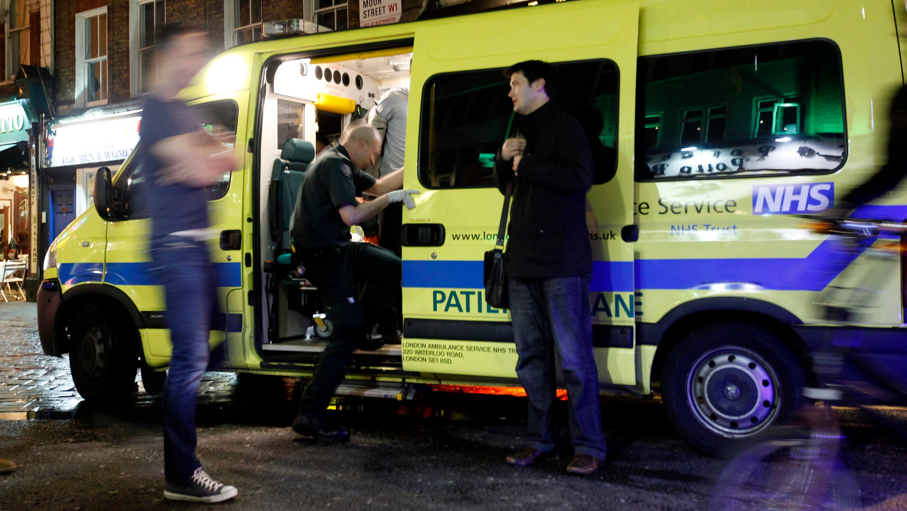 April 21: A man is taken into the ambulance, known as a 'booze bus,'  dedicated to keeping drunk people out of trouble on the streets, and out of hospital emergency rooms in the Soho area of central London.