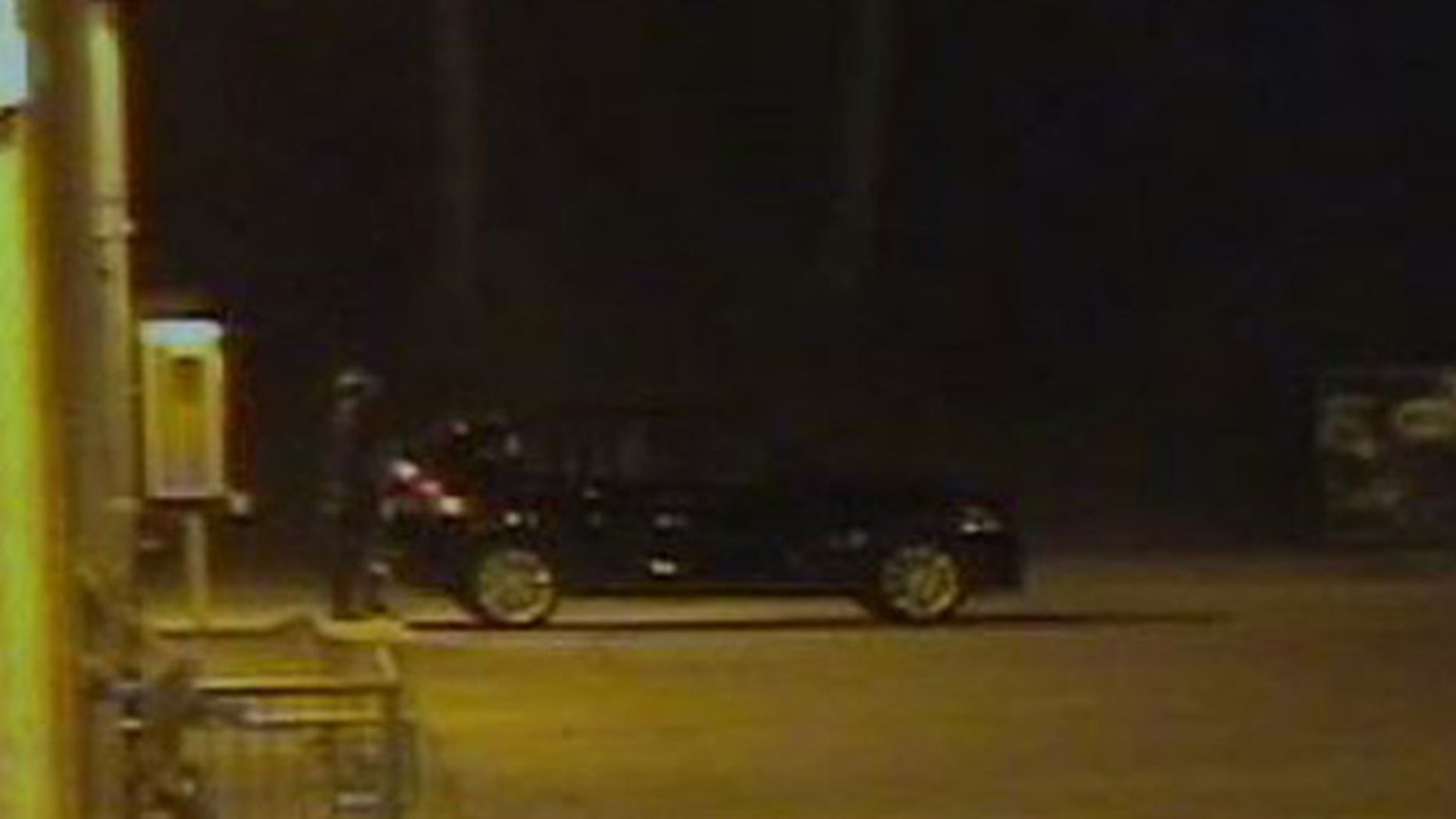 Surveillance images obtained by FOX25 show an unknown man near the Lincoln Stoddard Army Reserve Center, standing beside a dark BMW hatchback with sport rims.