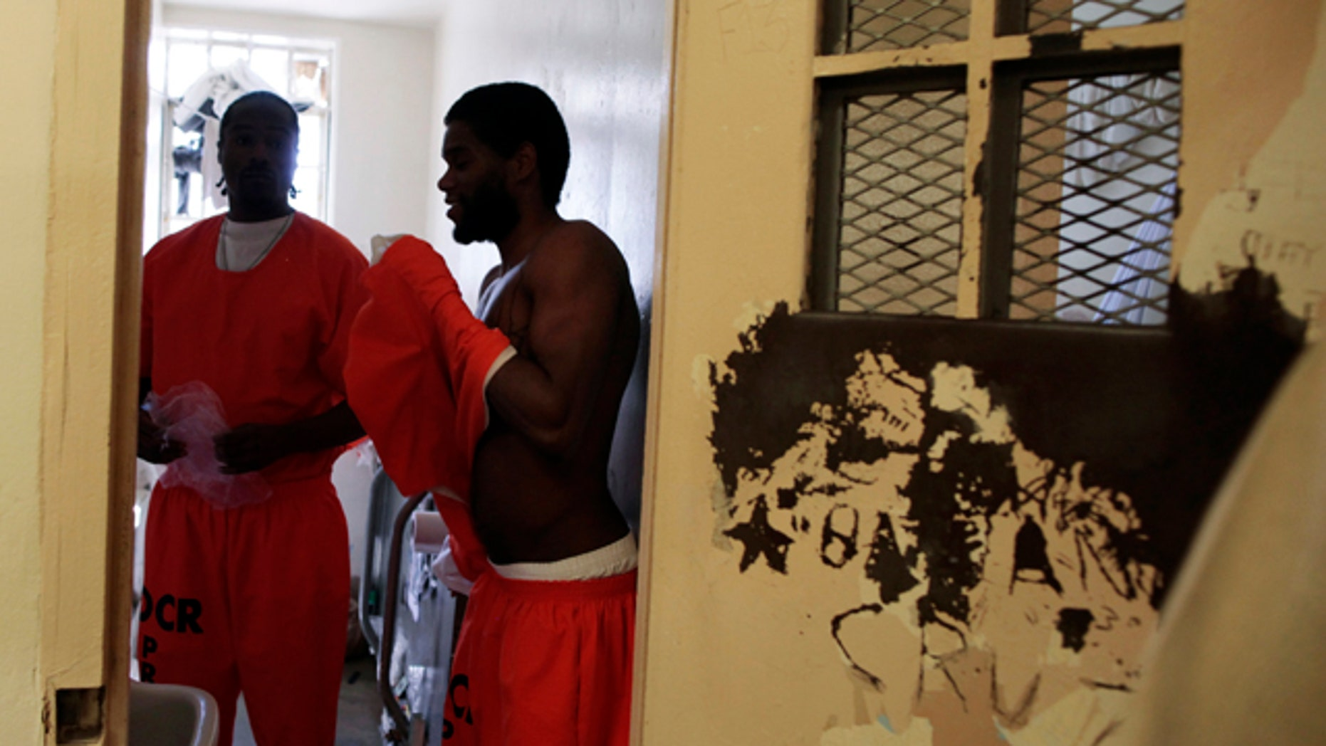 """Inmates Anthony Turner, 46, (L) who said he is serving 25 years to life for a three strikes offense, and Daniel King, 23 stand in their cell at the California Institution for Men state prison in Chino, California, June 3, 2011. The Supreme Court has ordered California to release more than 30,000 inmates over the next two years or take other steps to ease overcrowding in its prisons to prevent """"needless suffering and death."""" California's 33 adult prisons were designed to hold about 80,000 inmates and now have about 145,000. The U.S. has more than 2 million people in state and local prisons. It has long had the highest incarceration rate in the world."""