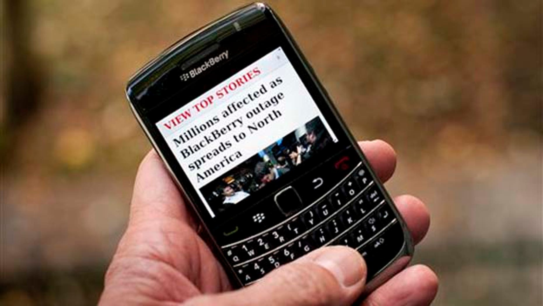 Oct. 12, 2011: A Blackberry user reads a story about a Blackberry outage that is affecting millions of users of the smartphone that has now spread to North America Wednesday in Montreal. Sporadic outages of BlackBerry messaging and email service spread to the U.S. and Canada on Wednesday, as problems stretched into the third day for Europe, Asia, Latin America and Africa.