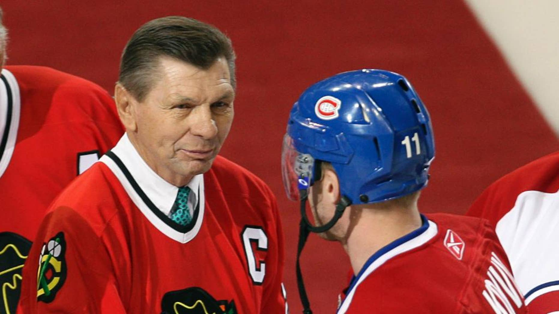 """FILE - In this Jan. 8, 2008, file photo, Montreal Canadiens captain Saku Koivu (11) talks with Chicago Blackhawks great Stan Mikita during a pregame ceremony in Montreal. Mikita's family says the Blackhawks Hall of Famer has been diagnosed with a suspected brain disorder, adding that the 74-year-old is """"facing some serious health issues"""" and has suspected Lewy body dementia. (AP Photo/The Canadian Press, Paul Chiasson, File)"""