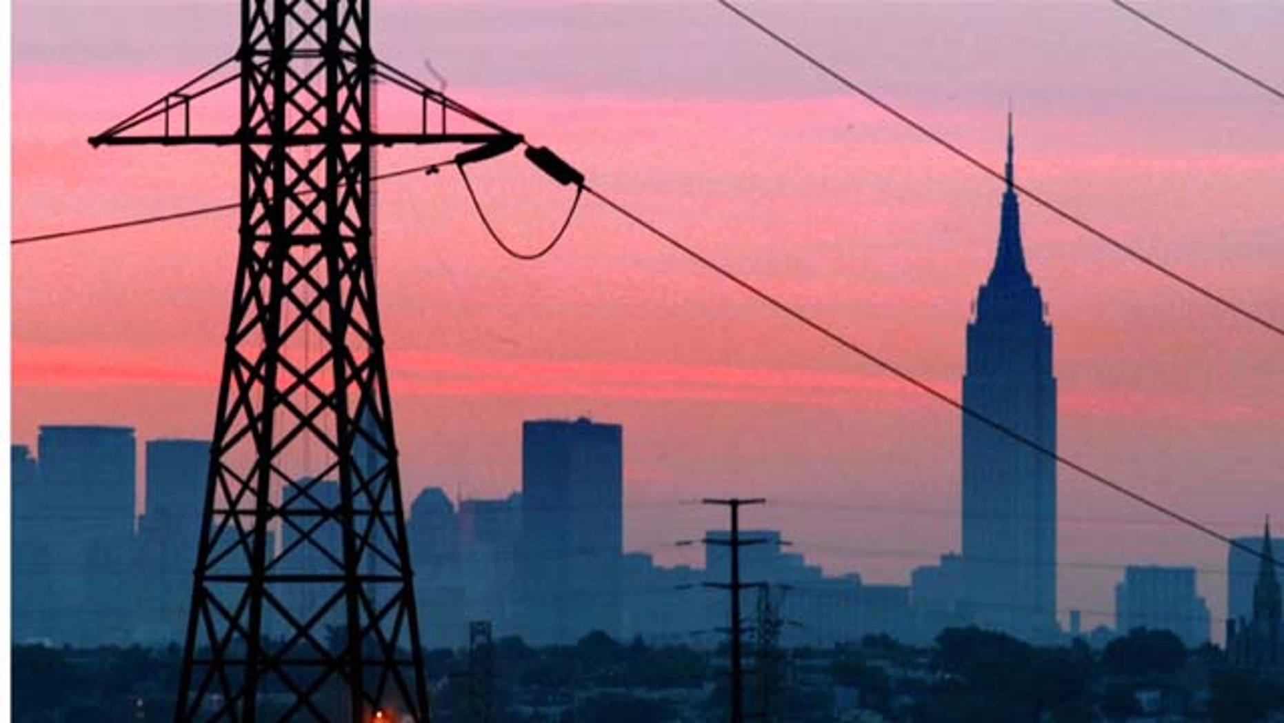 FILE - In a Friday, Aug. 15, 2003 file photo, the Empire State Building towers over the skyline of a blackout-darkened New York City just before dawn. Power lines from Jersey City, N.J., are in foreground.  (AP Photo)