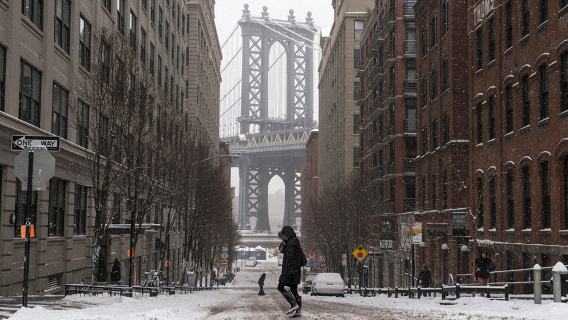 The Manhattan Bridge is seen in the background as commuters make their way through the streets of Dumbo after a snow storm in New York Jan. 27, 2015.