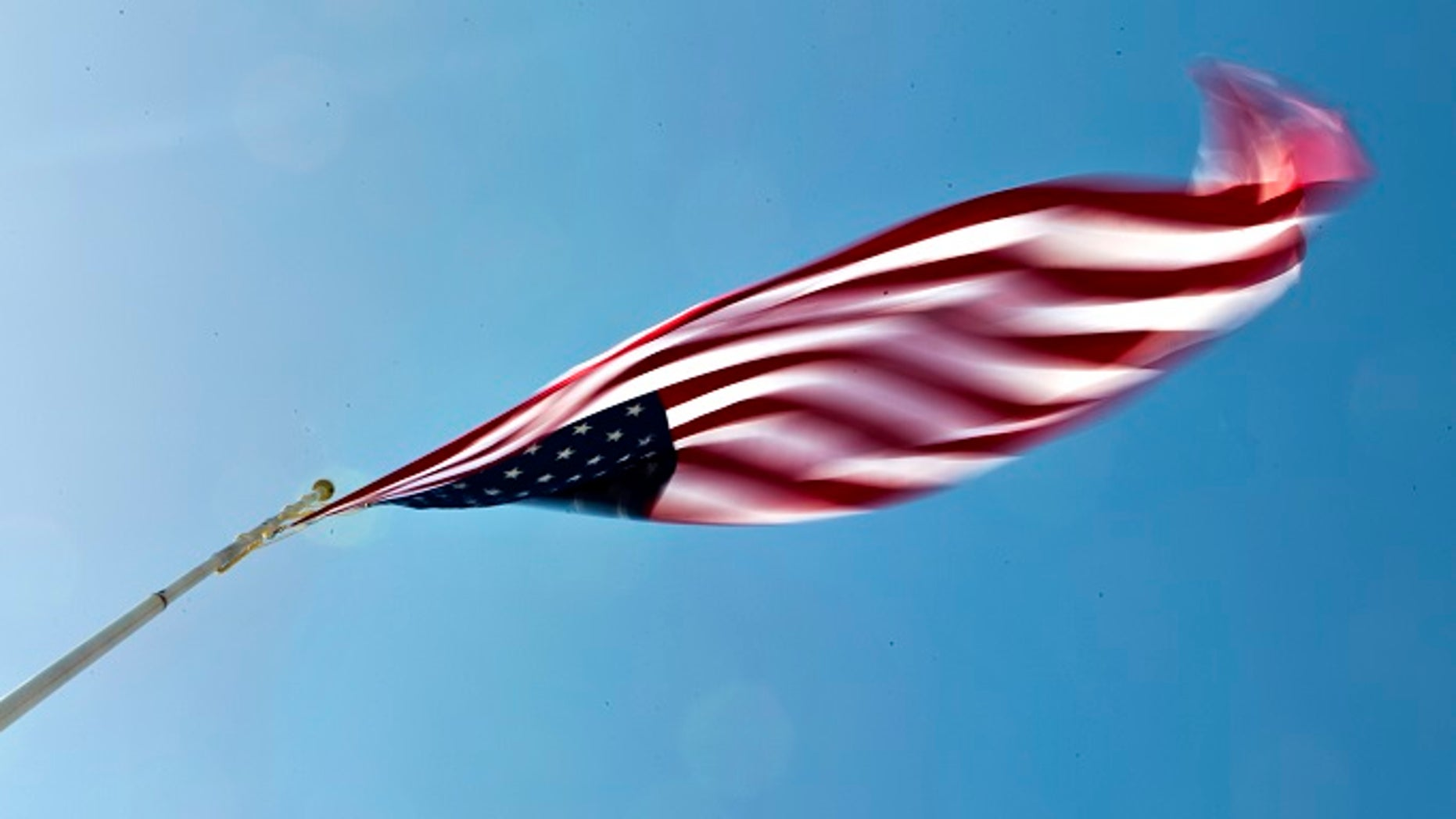 A large American flag blows wildly in the wind at the Terrible Herbst station in the Las Vegas area are predicted to go as high as 50 mph on Tuesday, April, 14, 2015.(L.E. Baskow/Las Vegas Sun via AP)
