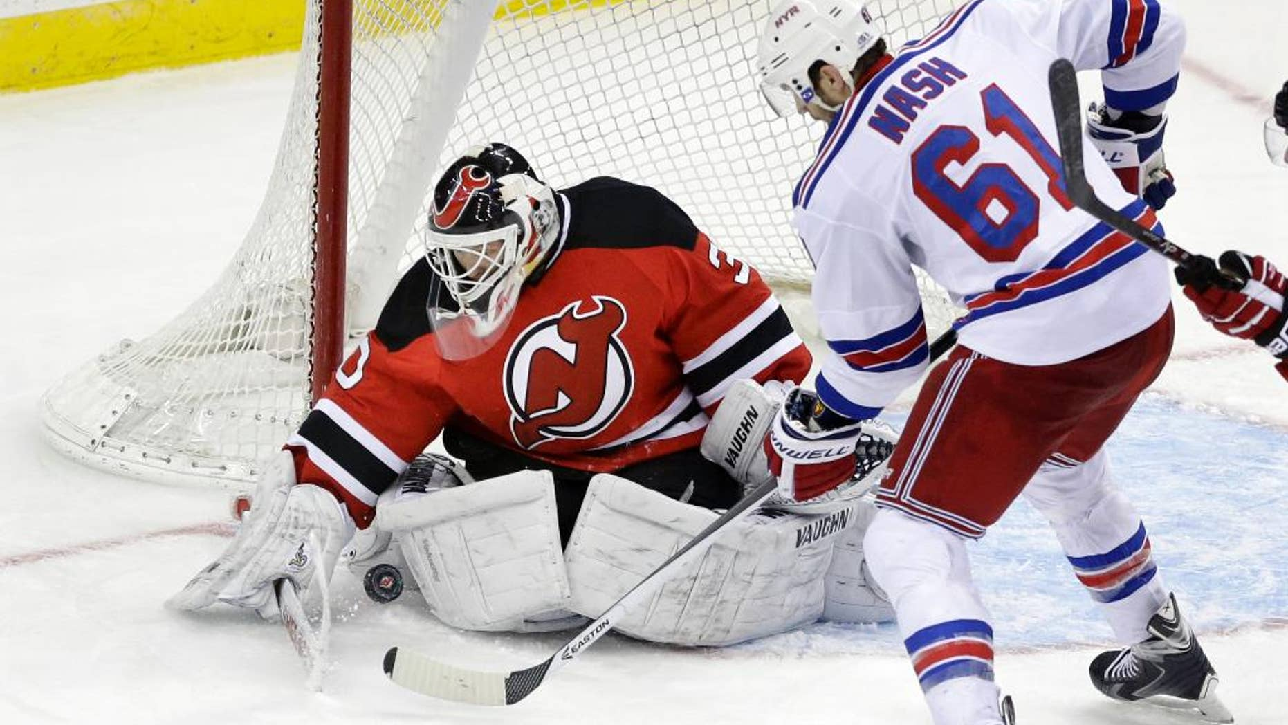 FILE - In this March 22, 2014, file photo, New Jersey Devils goalie Martin Brodeur (30) stops a shot by New York Rangers' Rick Nash (61) during the third period of an NHL hockey game in Newark, N.J. Brodeur wasn't ready to call it a career at 42 after the Devils chose not to re-sign him. But he didn't get any offers until Blues general manager Doug Armstrong called Brodeur's agent on Tuesday, Nov. 25, after goalie Brian Elliott sustained a lower-body injury in the Blues' 3-2 shootout loss to the Ottawa Senators. Brodeur, who leads the NHL in wins (688), games played (1,259), losses (394) and shutouts (124), took part in the morning skate Friday with the Blues, who will face the Edmonton Oilers. (AP Photo/Mel Evans, File)