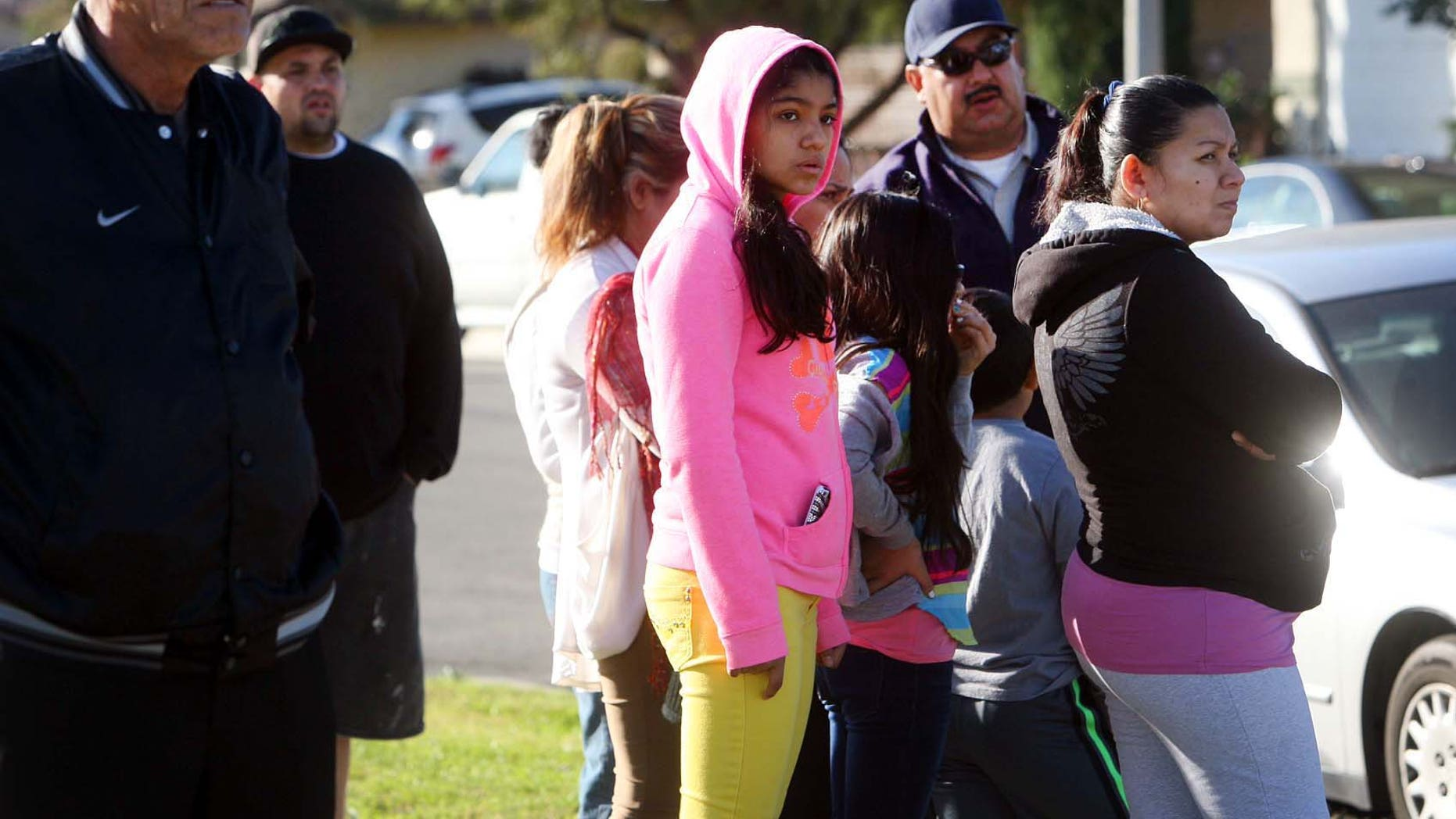 Neighbors look on as police investigate house where a family of four were found shot to death.