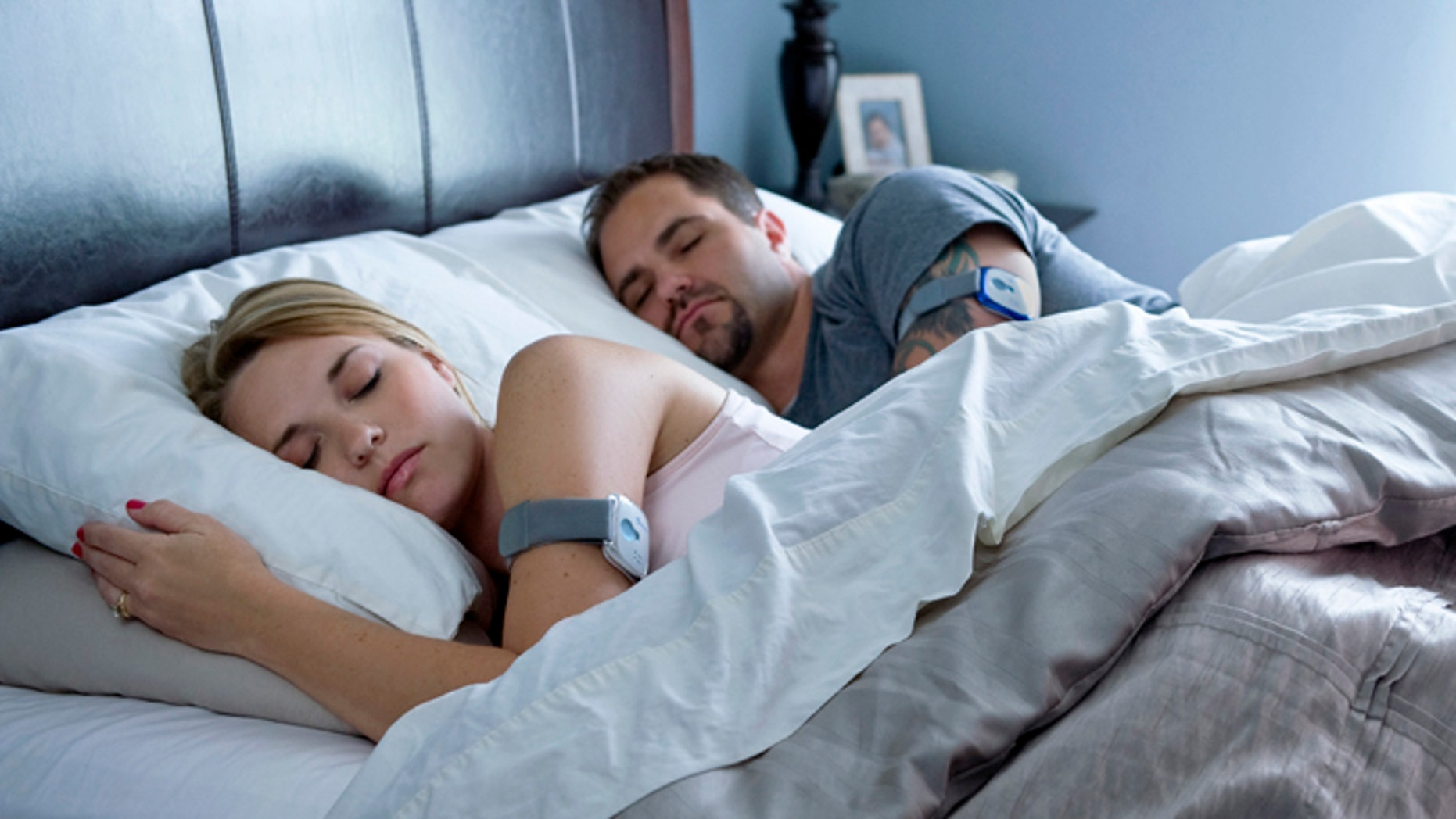 A couple sleeps while wearing the BodyMedia FIT