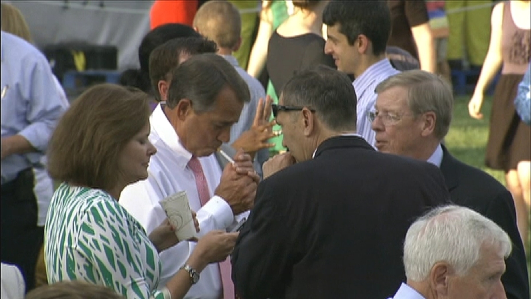 In this video frame from the White House congressional picnic on Wednesday, House Speaker John Boehner lights up.