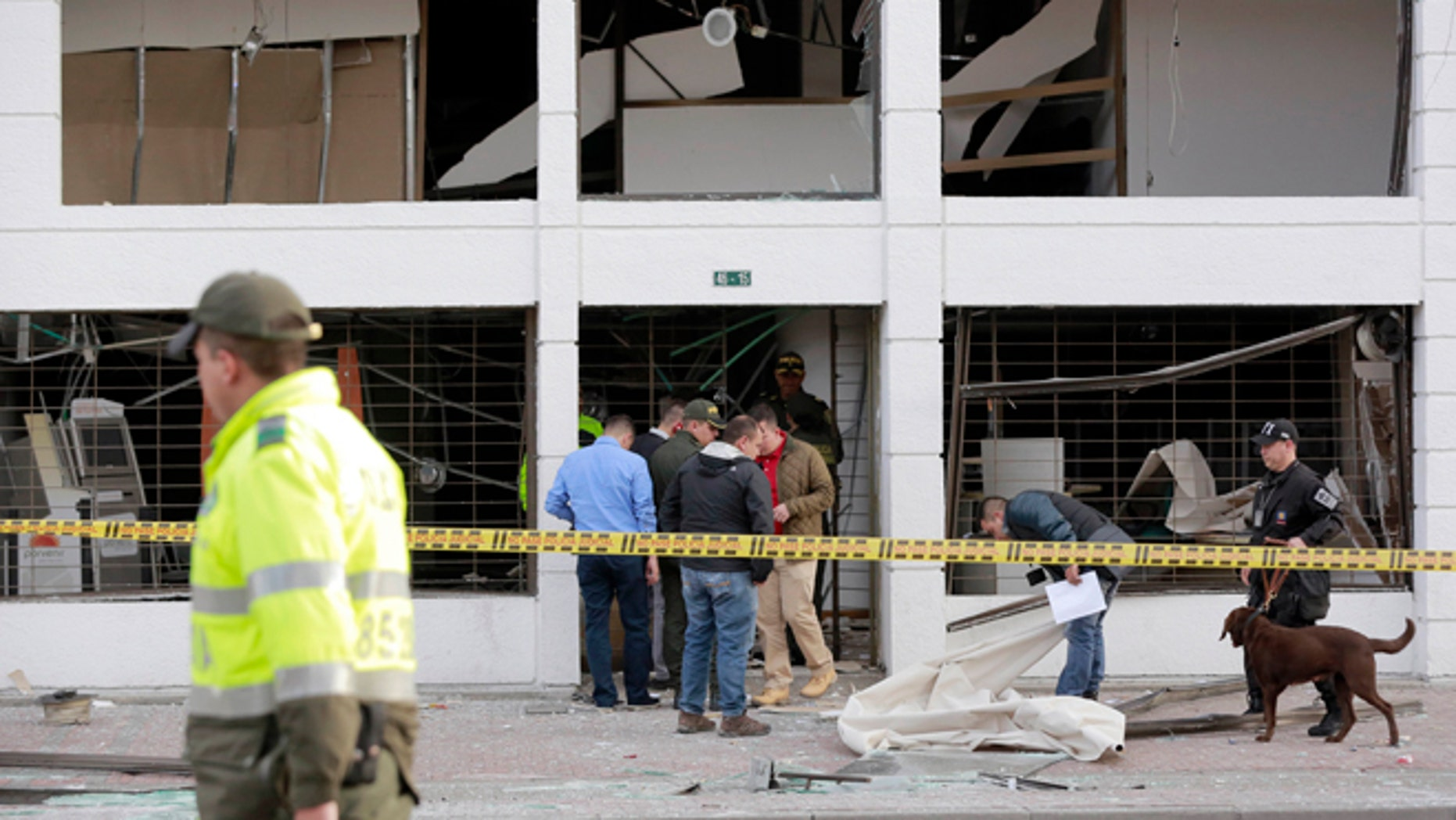 Police officers inspect an office after it was wrecked by an explosion in Bogota, Colombia, Thursday, July 2, 2015. A homemade explosive device went off in the financial district of Colombia's capital and wounded several people, while a second blast elsewhere in Bogota injured another, authorities said. (AP Photo/Fernando Vergara)