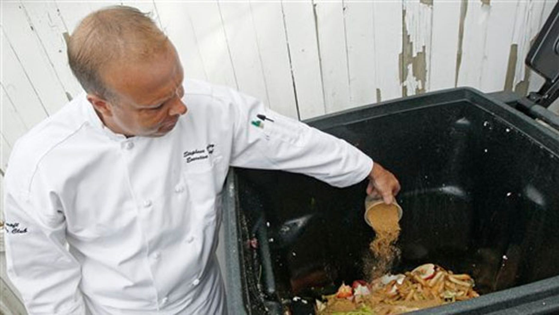 June 11, 2012: Executive chef Stephane Baloy scatters a mixture of microorganisms onto a container of composting scrap food at the Ferncroft Country Club in Middleton, Mass.