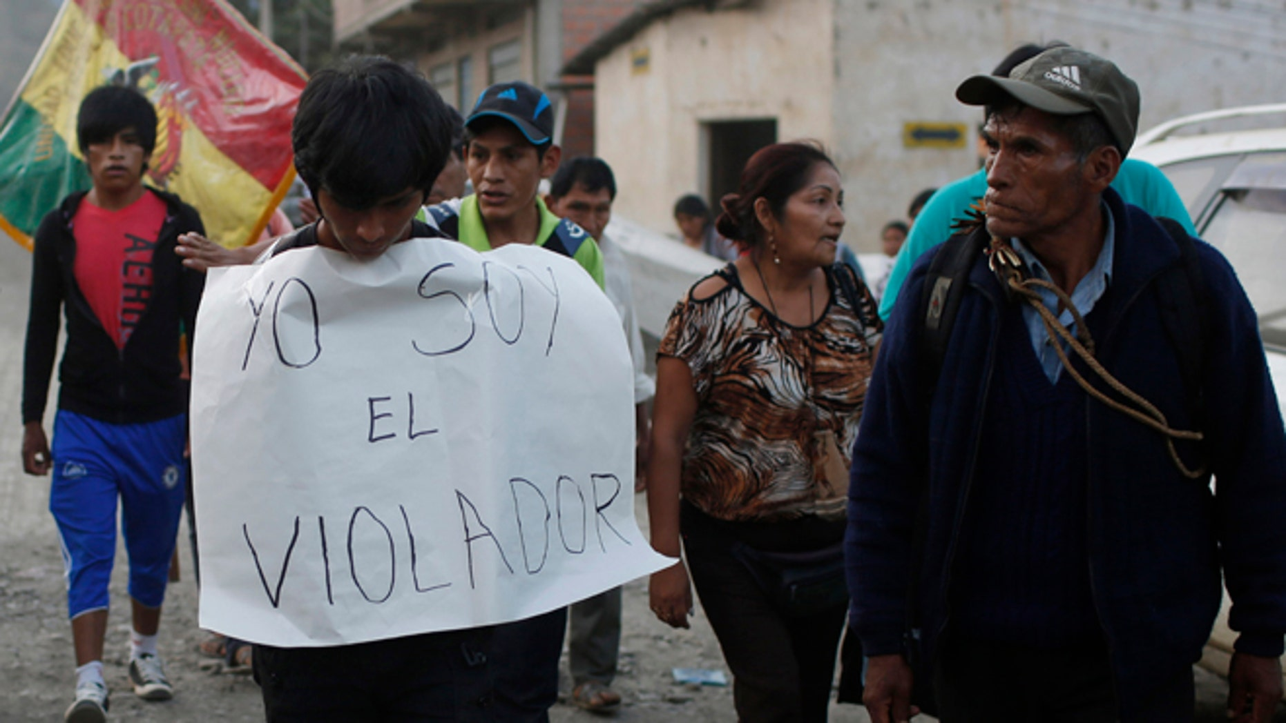 "In this June 6, 2015 photo, a man is made to wear a sign with a handwritten message that reads in Spanish; ""I'm the rapist,"" as he is paraded through La Asunta, northeast of La Paz, Bolivia. Groups of citizens patrol the town of 7,000 people, who have imposed a sort of vigilante dry law in the coca-growing mountain town,  hoping to end a series of rapes and other crimes. In recent months an 11-year-old girl, and 12-year old girl have been victims of rape in La Asunta, according to local officials. (AP Photo/Juan Karita)"