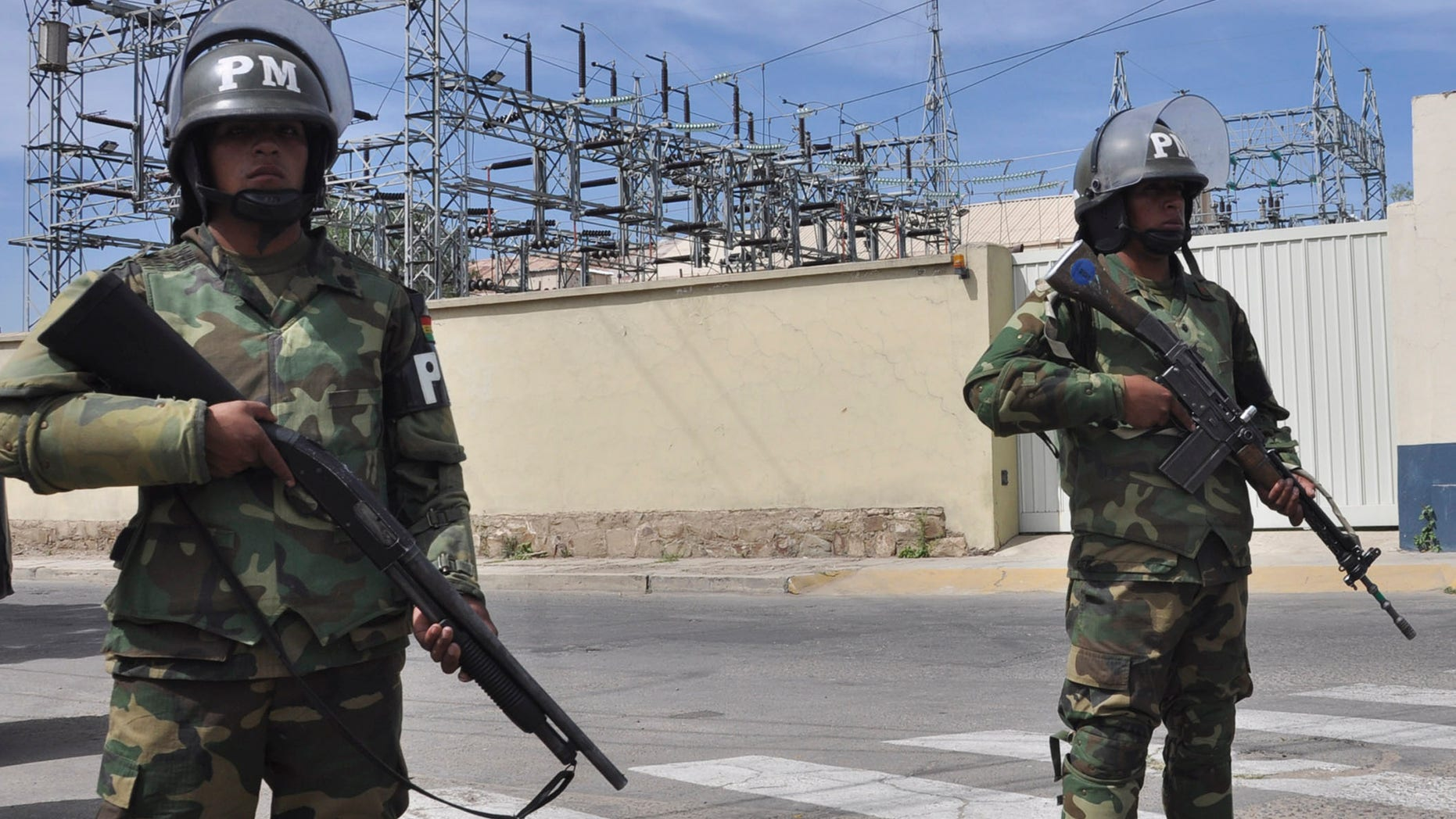 Military police stand guard outside Transportadora de Electricidad, the Spanish electricity grids Bolivian subsidiary, in Cochabamba, Bolivia, Tuesday, May 1, 2012. Bolivia's President Evo Morales says his government is completing the nationalization of the country's electricity industry by taking over its electrical grid from the Spanish-owned company, Red Electrica. (AP Photo)