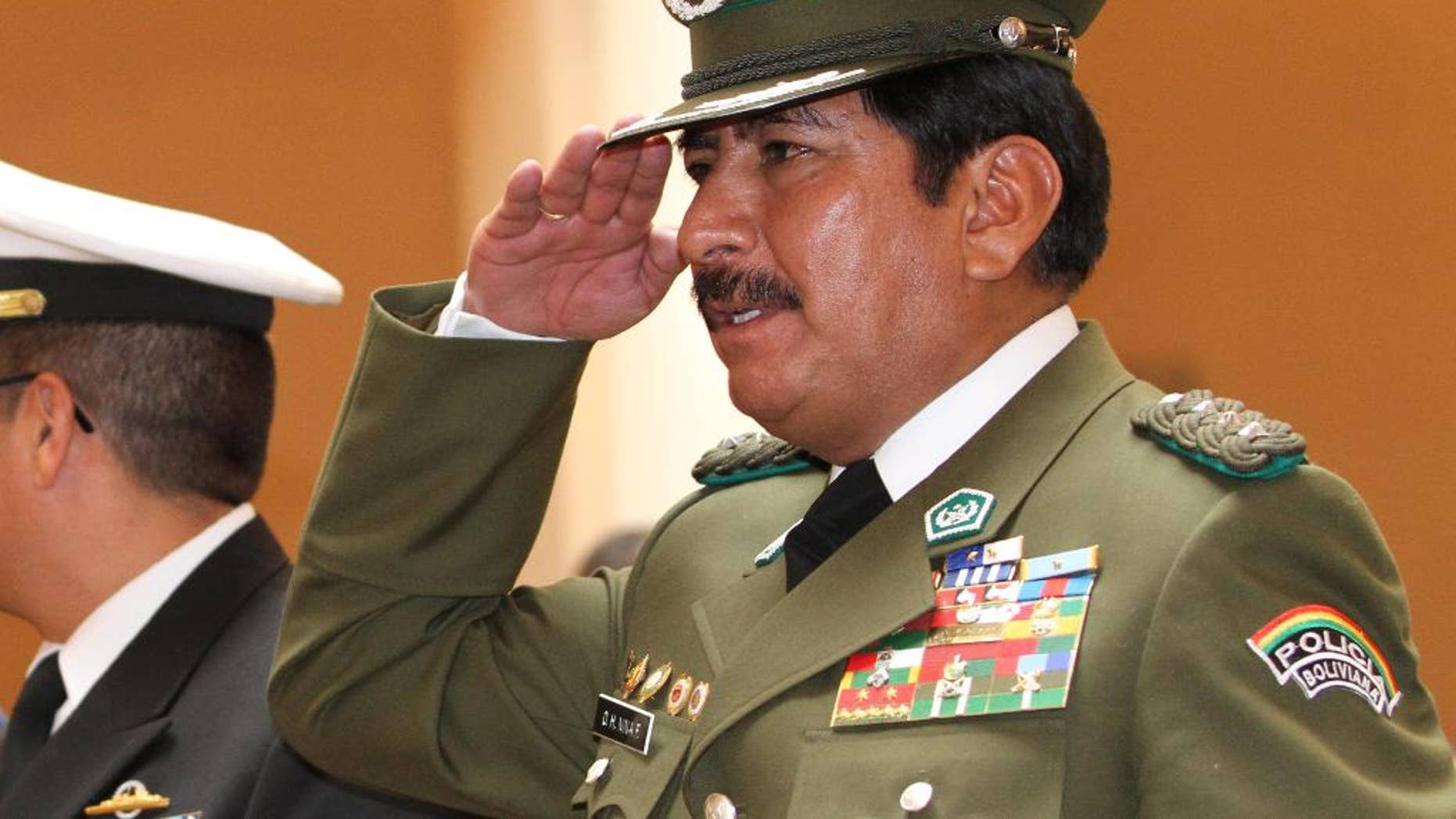 In this Jan. 24, 2010 photo, Bolivia's National Police Chief Col. Oscar Nina salutes during his swearing-in ceremony at the government palace in La Paz, Bolivia. One year prior, Nina was named anti-drug police chief. In March of 2015, the retired police general who reorganized Bolivia's counter-narcotics force after President Evo Morales expelled U.S. drug agents, is under investigation for illicit enrichment and drug trafficking ties. A judge was to decide Wednesday, March 4, 2015 whether Gen. Nina should be jailed. (AP Photo/Juan Karita)