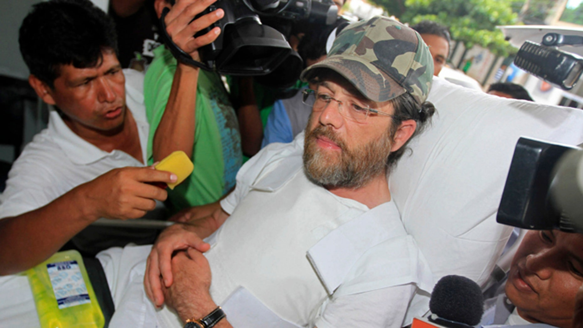 Members of the press surround U.S. businessman Jacob Ostreicher as he arrives in a hospital bed wearing a flak jacket to his court hearing in Santa Cruz, Bolivia, Tuesday, Dec. 11, 2012. A Bolivian appeals panel has refused to immediately release Ostreicher, despite evidence he was fleeced and extorted by prosecutors who have had him jailed for 18 months without charges on suspicion of money laundering. Ostreicher has been hospitalized for more than two weeks in a private clinic after being diagnosed with Parkinsons. (AP Photo)