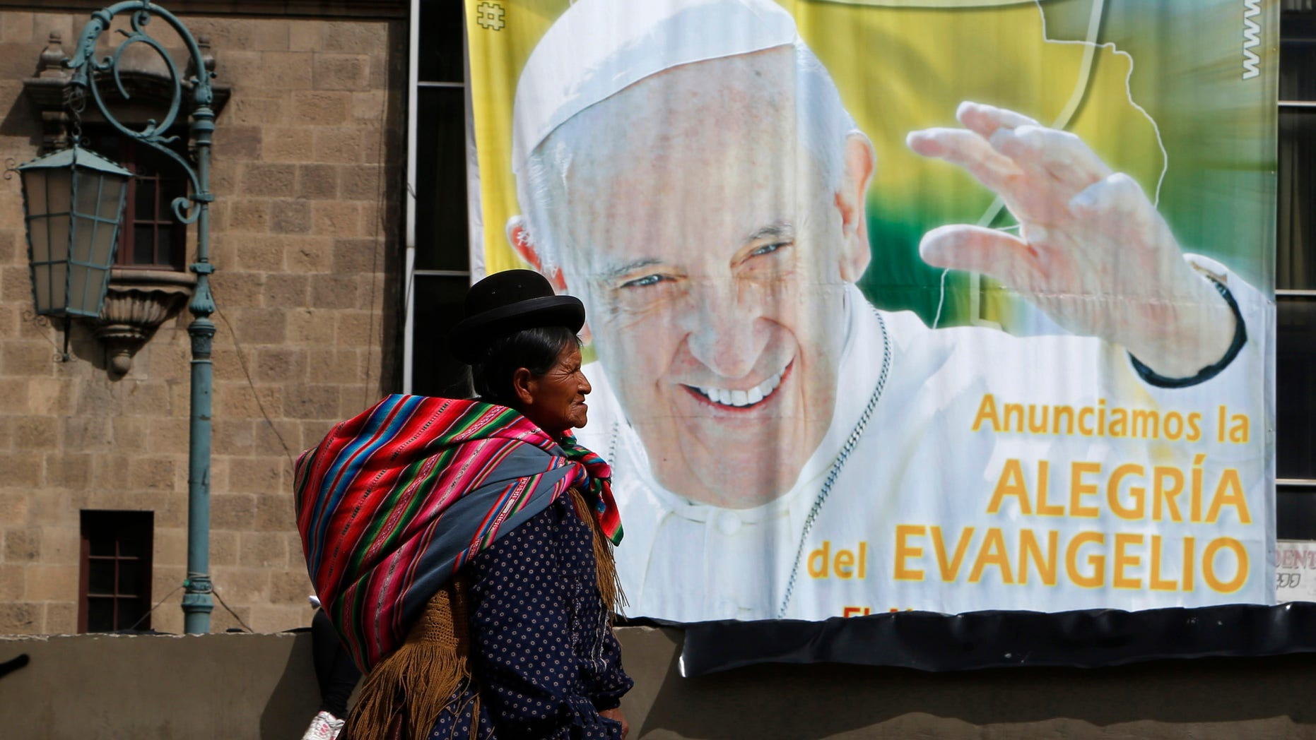 "An Aymara indigenous woman walks past a billboard featuring Pope Francis with a message that reads in Spanish: ""Announcing the joy of the Gospel"" in La Paz, Bolivia, Friday, July 3, 2015. The pope's trip to South America that includes Bolivia is set for July 5-12, though he will only spend four hours in Bolivia's capital due to the altitude, church officials say. (AP Photo/Juan Karita)"