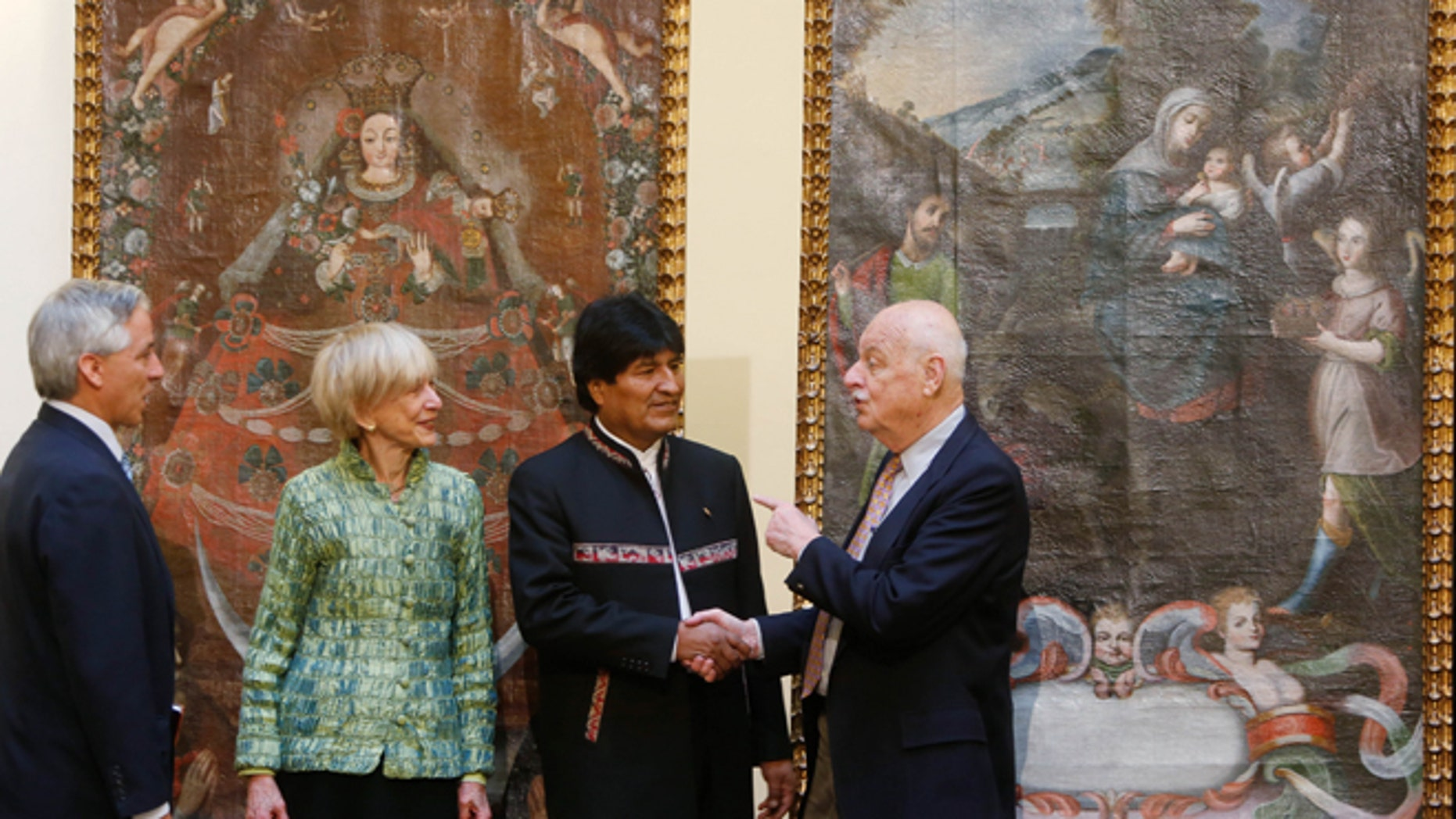 "Backdropped by the paintings ""Virgin of Candelaria,"" and  ""Escape to Egypt,"" Bolivia's President Evo Morales, second from right, shakes hands with Richard Huber, right, as Roberta Huber, second from left, and Bolivia's Vice President Alvaro Garcia, watch, during a ceremony recognizing the return of the stolen art, at the government palace, in La Paz, Bolivia, Thursday, April 9, 2015. Avid collectors, the Hubers returned the art work after learning from a museum that the two large paintings had been reported stolen from a Catholic church in southern Bolivia. (AP Photo/Juan Karita)"