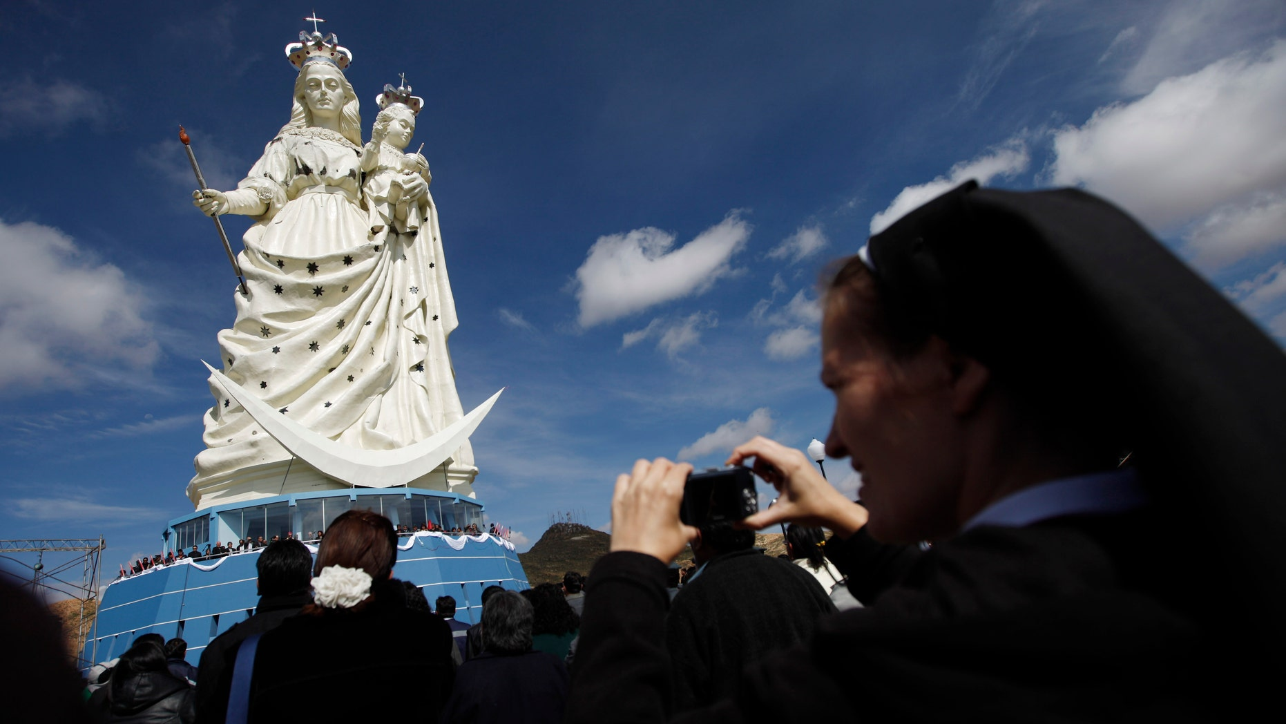 """A nun takes pictures of a newly unveiled statue of the Virgin Mary holding a baby Jesus on Santa Barbara hill in the mining city of Oruro, Bolivia. The 45 meter (147 feet) statue that took four years to build, known in Spanish as """"Virgen del Socavón,"""" or the Virgin of the Tunnel, is Oruro's patron, venerated in particular by miners and folkloric Carnival dancers. (AP Photo/Juan Karita)"""
