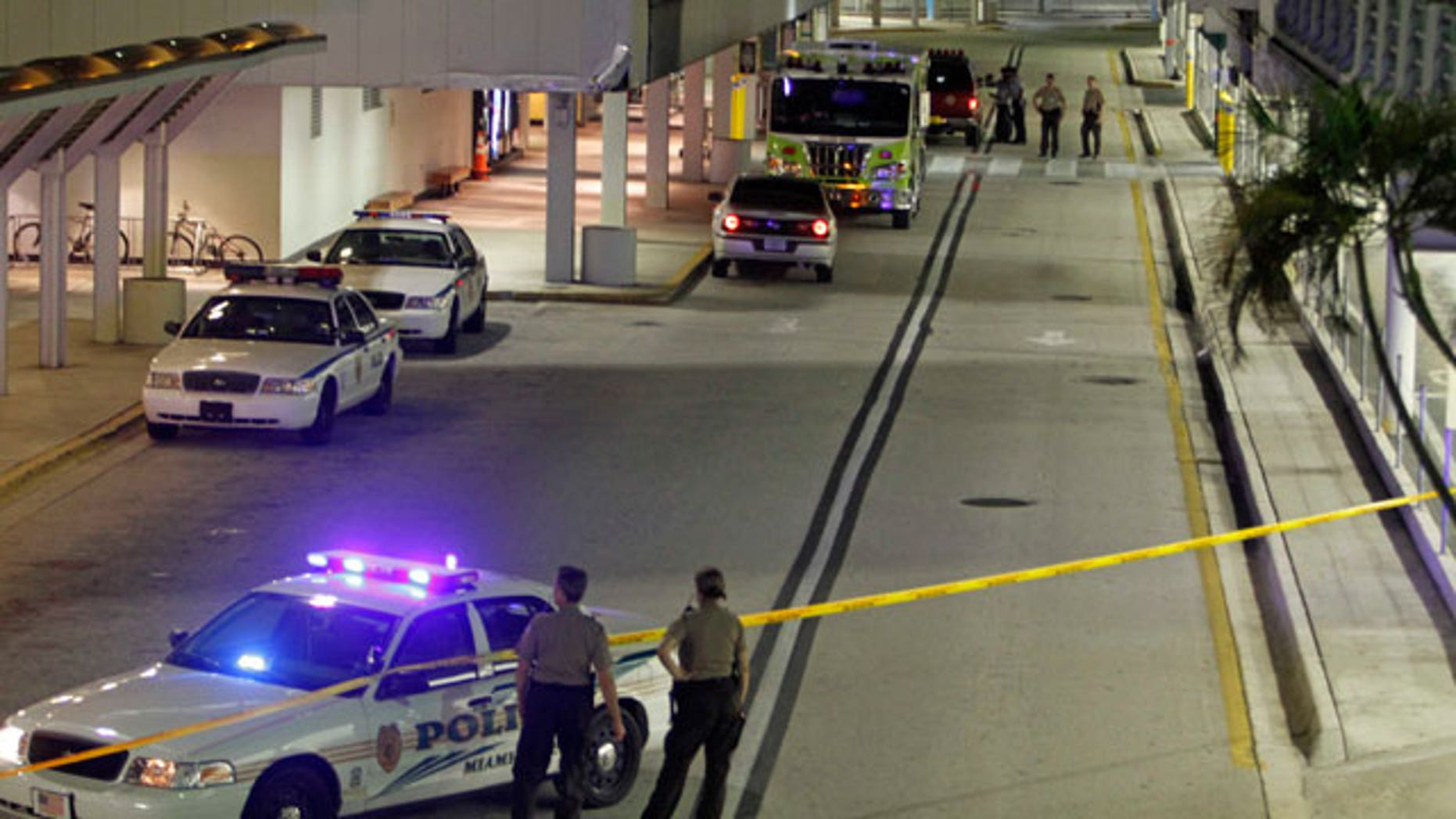A Miami-Dade Police and Fire Rescue officers are seen on the arrival level at Miami International Airport in Miami, early morning Friday, Sept. 3, 2010. A spokesman for Miami International Airport says four of its six concourses have been evacuated as a police bomb squad investigates a report of a suspicious item. Several flights were diverted to other parts of the terminal.