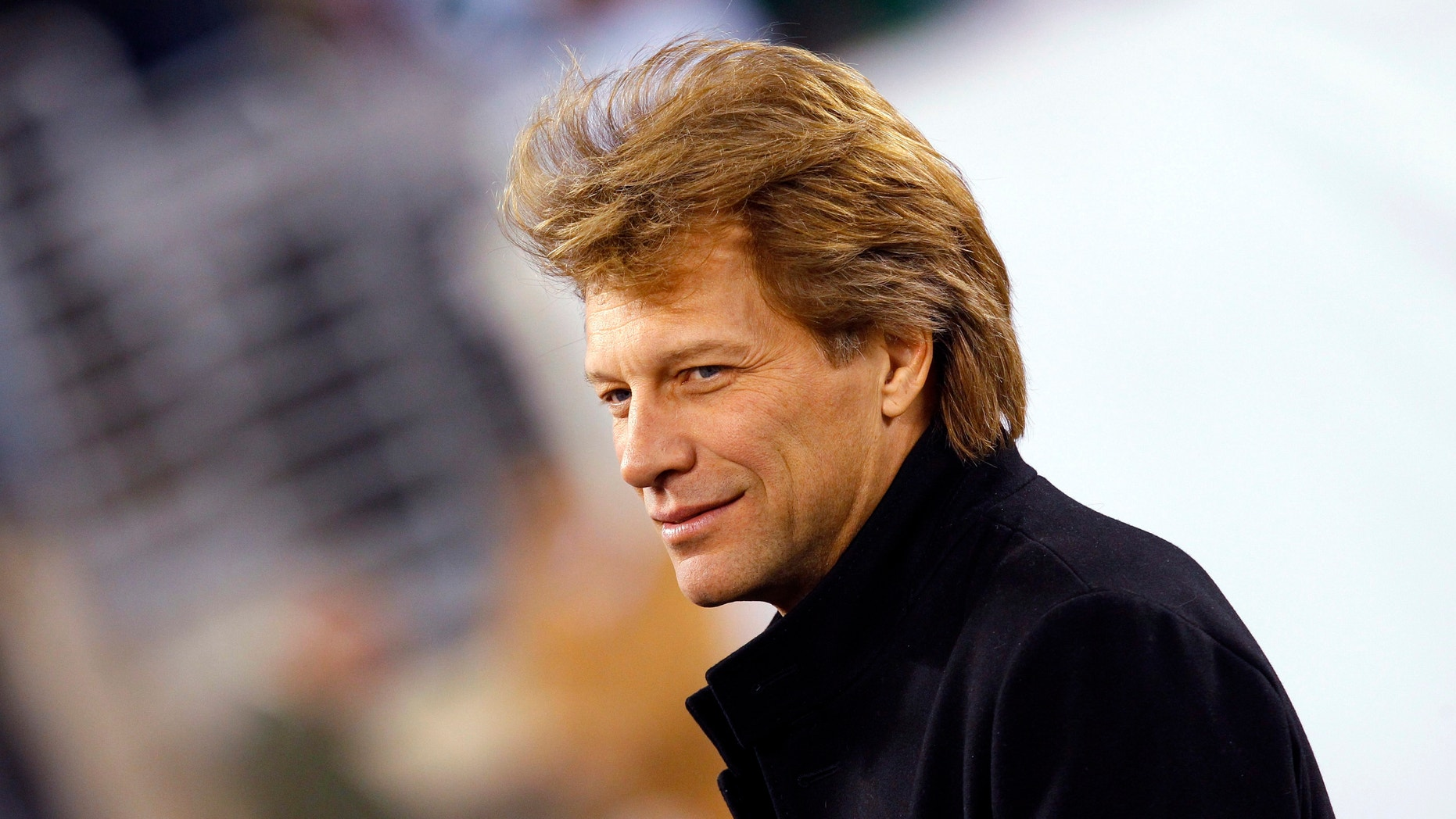 Musician Jon Bon Jovi walks on the field before the NFL football game between the New England Patriots and the New York Jets in East Rutherford, New Jersey, November 13, 2011.