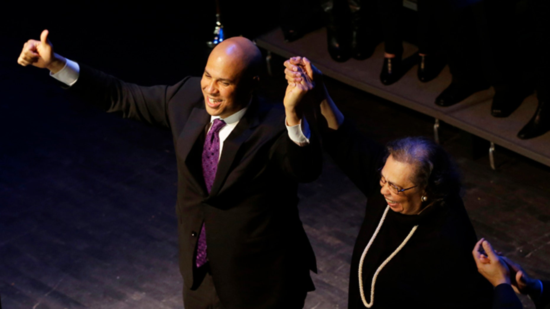 Wednesday, Oct. 16, 2013: Newark Mayor Cory Booker, left, holds the hand of his mother Carolyn Booker after his victory speech during an election night party, Newark, N.J.
