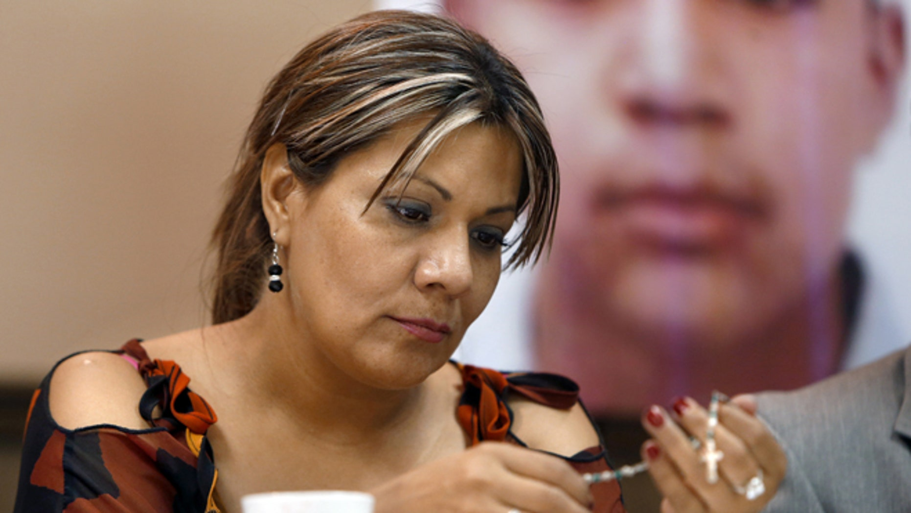 Araceli Rodríguez handles a rosary during a news conference in Nogales, Mexico, that belonged to her son José Antonio Elena Rodríguez, pictured behind her, who was shot and killed by U.S. Border Patrol agent in October 2012. Federal authorities have charged a U.S. Border Patrol agent who killed a Mexican teenager in a cross-border shooting with second-degree murder. Luis Parra, the attorney for the mother of Jose Antonio Elena Rodriguez, told The Associated Press that a federal grand jury on Wednesday, Sept. 23, 2015, indicted agent Lonnie Swartz. (Kelly Presnell/Arizona Daily Star via AP,File)