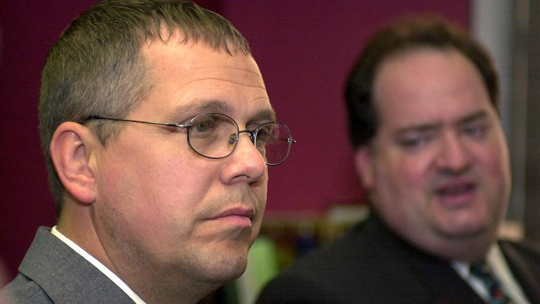 File-This Sept. 8, 2005, file photo shows Customs and Border Protection Officer Robert Rhodes listening to his defense attorney, Steven Cohen, during a press conference after the verdict from the U.S. Federal Courthouse in Buffalo, N.Y. The United States is defending itself against a Chinese tourist's $10 million injury claim with the testimony of a surprising witness  a border officer the government initially fired and charged in the case. Rhodes says he was eager to testify in the lawsuit filed by Zhao Yan, being tried now in Rochester, even though the government's prosecution of him left him bankrupt. He says he was glad to be able to tell his side of the story. (AP Photo/Don Heupel, File)
