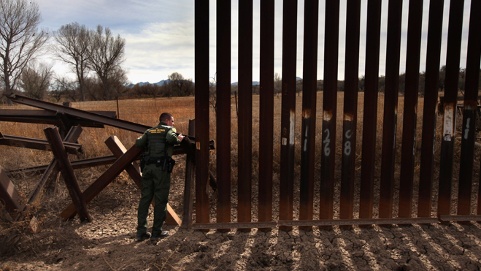 U.S. Border Patrol agent Richard Funke inspects the juction of the new and old border fence at the U.S.- Mexico border on December 7, 2010 near Nogales, Arizona. (Photo by John Moore/Getty Images)