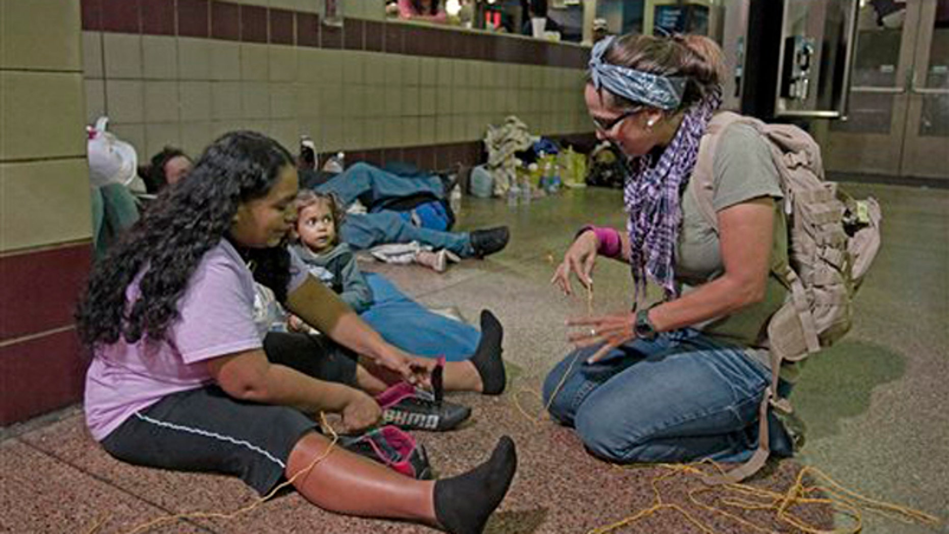 Volunteer Michelle Lewis of Phoenix, right, helps Doris Suyapa, of Honduras, with her shoes, by using yellow rope for shoe laces, Thursday, May 29, 2014 at the Greyhound bus terminal in Phoenix.  About 400 mostly Central American women and children caught crossing from Mexico into south Texas were flown to Arizona this weekend after border agents there ran out of space and resources.  Officials then dropped hundreds of them off at Phoenix and Tucson Greyhound stations, overwhelming the stations and humanitarian groups who were trying to help. (AP Photo/Rick Scuteri)