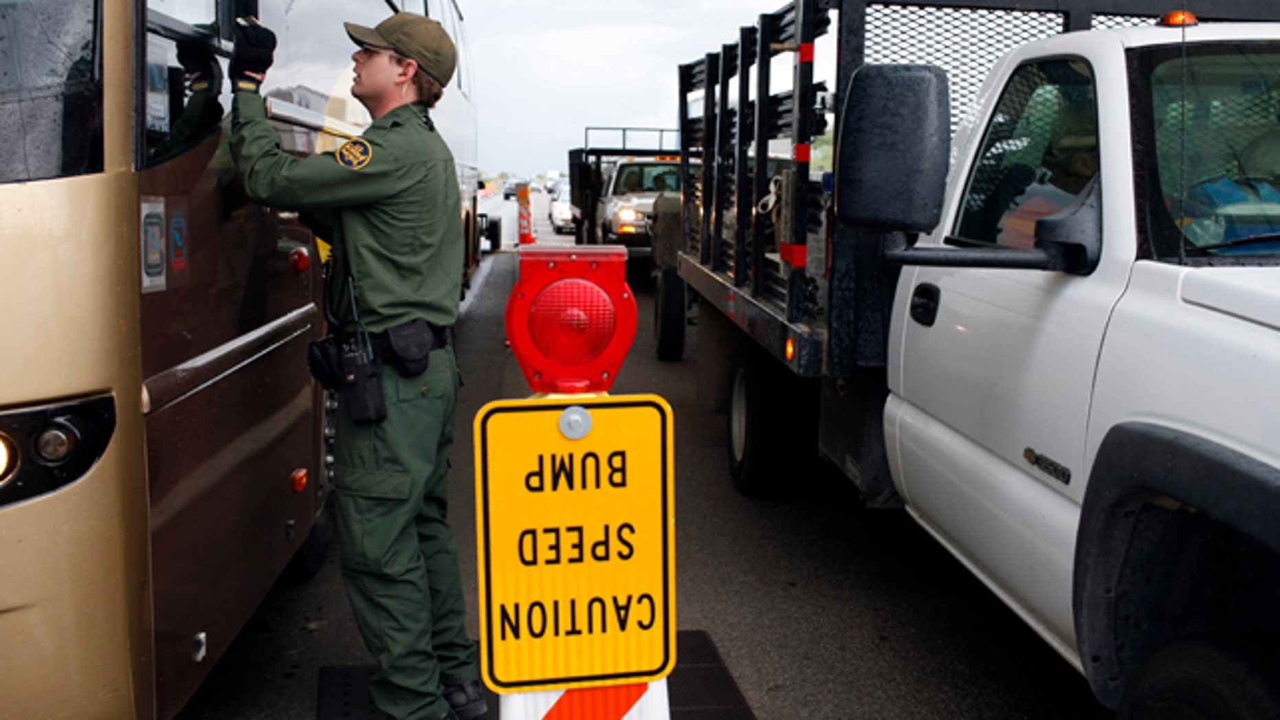 FILE - This July 29, 2010 file photo shows a Border Patrol agent checking the identification card of a bus driver at a checkpoint in Amado, Ariz. The American Civil Liberties Union reported Wednesday Jan. 15, 2014 that border patrol agents at checkpoints across southern Arizona are routinely violating the constitutional rights of U.S. residents, including unjustified detentions and illegal searches as a pretext to investigating other criminal activity in violation of the agency's mandate that stops be limited to inquiring about citizenship and visually inspecting vehicles.  (AP Photo/Jae C. Hong, file)