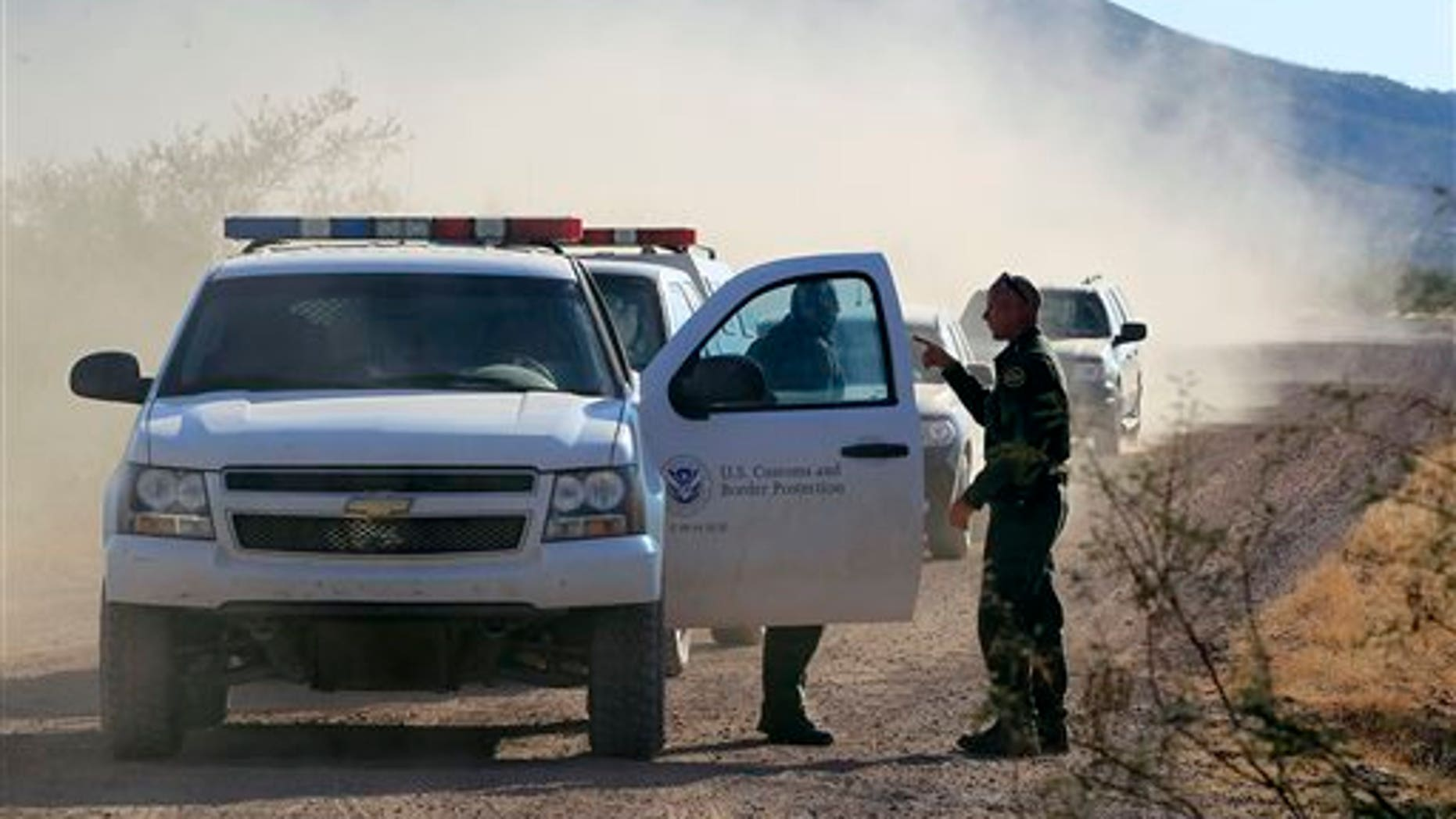FILE - In this Oct. 2, 1012 file photo, several U.S. Customs and Border Protection officers and other law enforcement jurisdictions drive the roads near where a U.S. Border Patrol agent was shot and killed, and one other was shot and injured, where the shooting took place, near Bisbee, Ariz. Border Patrol agents in southern Arizona are subjecting U.S. citizens to illegal searches, detentions and excessive force in many cases miles from the state's border with Mexico, the American Civil Liberties Union wrote in a complaint Wednesday, Oct. 9, 2013. (AP Photo/Ross D. Franklin, file)