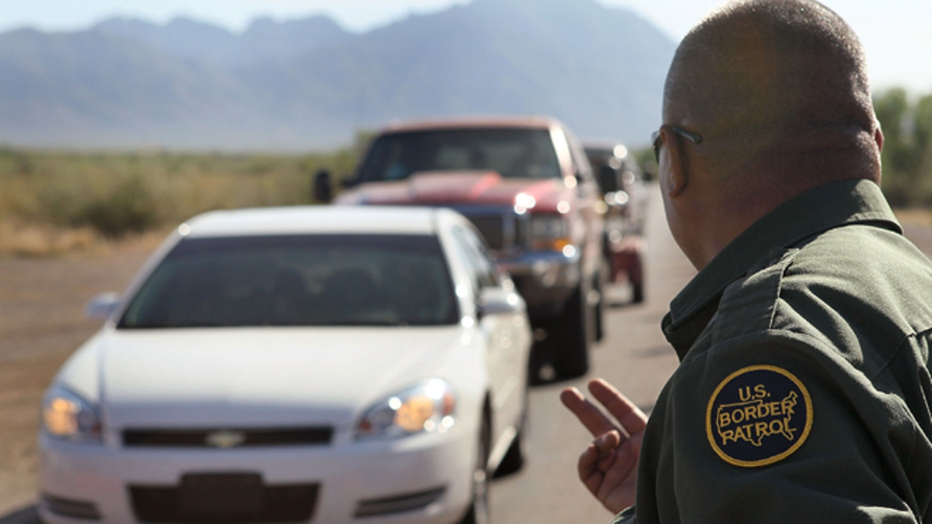 A Border Patrol agent checks vehicles for illegal immigrants and contraband at a roadside checkpoint June 1, 2010 near Sasabe, Arizona. (Photo by Scott Olson/Getty Images)