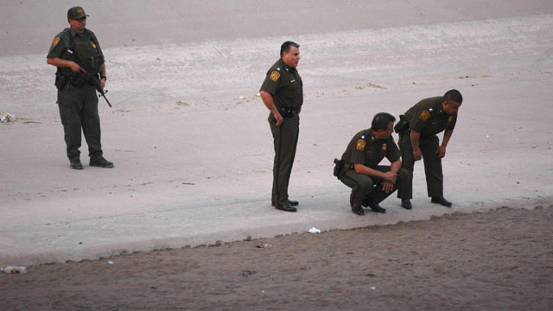 FILE - In this June 7, 2010, file photo, U.S. border patrol agents examine the area near where 14-year-old Mexican youth Sergio Adrian Hernandez Huereca was killed, allegedly shot by a U.S. Border Patrol agent after a confrontation under the Paso Del Norte border bridge in Ciudad Juarez, Mexico. (AP Photo)