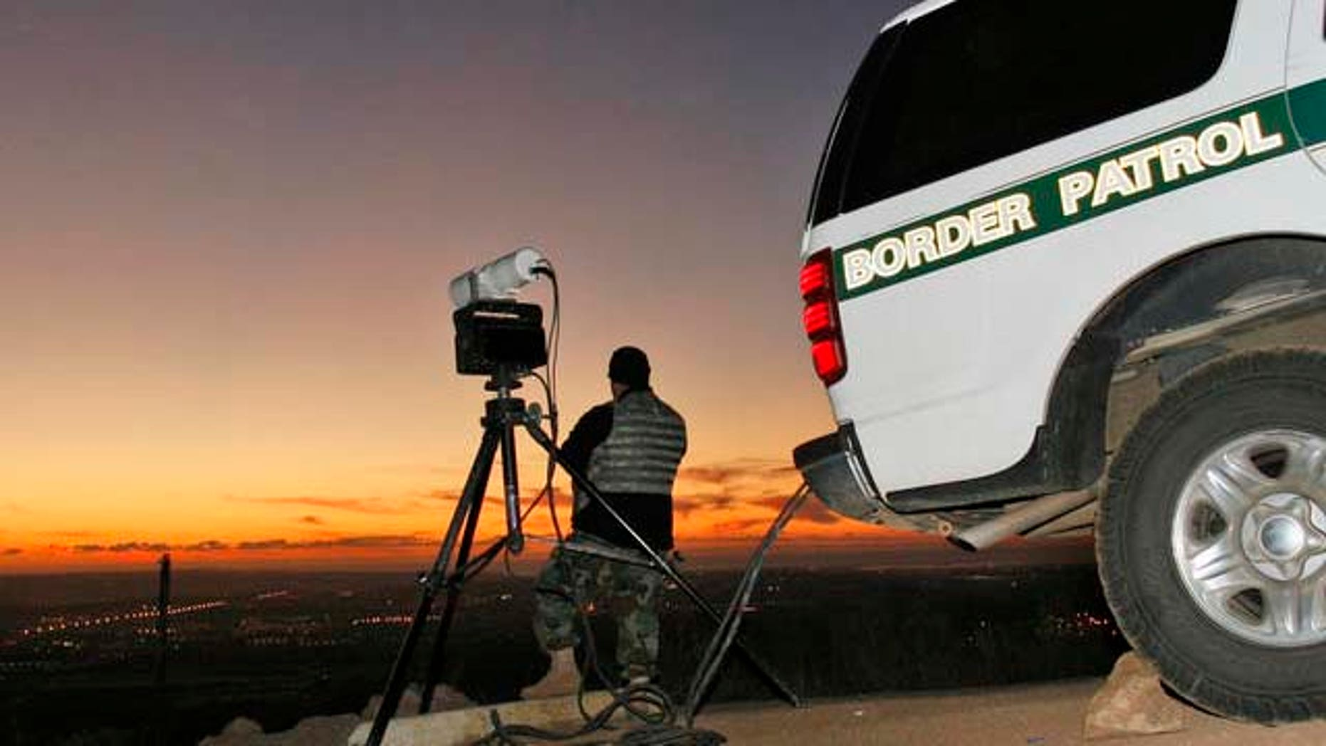 ** ADVANCE FOR SUNDAY, DEC. 31 **A National Guard soldier peers over the vast Otay Mountain Valley as he assists the Border Patrol infrared scope unit as agents search the area for smugglers in San Diego Wednesday, Dec. 20, 2006. The unit directs other agents in the area when they sight smugglers bringing illegal immigrants into the country.   (AP Photo/Lenny Ignelzi)