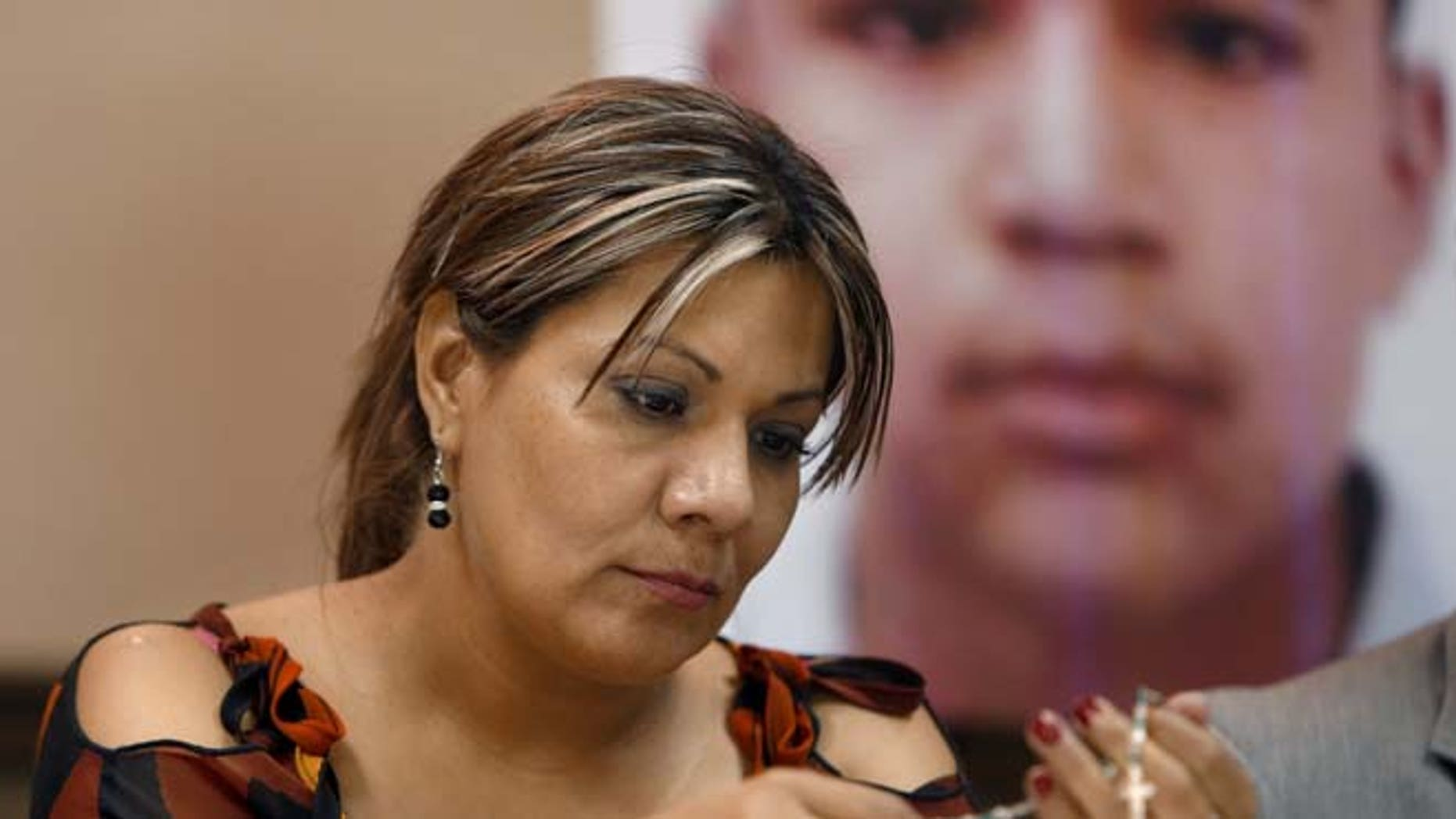 FILE - In this July 29, 2014, file photo, Araceli Rodriguez handles a rosary that belonged to her son Jose Antonio Elena Rodriguez, pictured behind her, who was shot and killed by U.S. Border Patrol agent in October 2012, during a news conference in Nogales, Mexico. The civil rights case against Agent Lonnie Swartz over the death of 16-year-old Jose Antonio Elena Rodriguez will go forward after U.S. District Court Judge Raner C. Collins denied a part of his motion to dismiss the case. (Kelly Presnell/Arizona Daily Star via AP)  ALL LOCAL TELEVISION OUT; PAC-12 OUT; MANDATORY CREDIT; GREEN VALLEY NEWS OUT; MANDATORY CREDIT