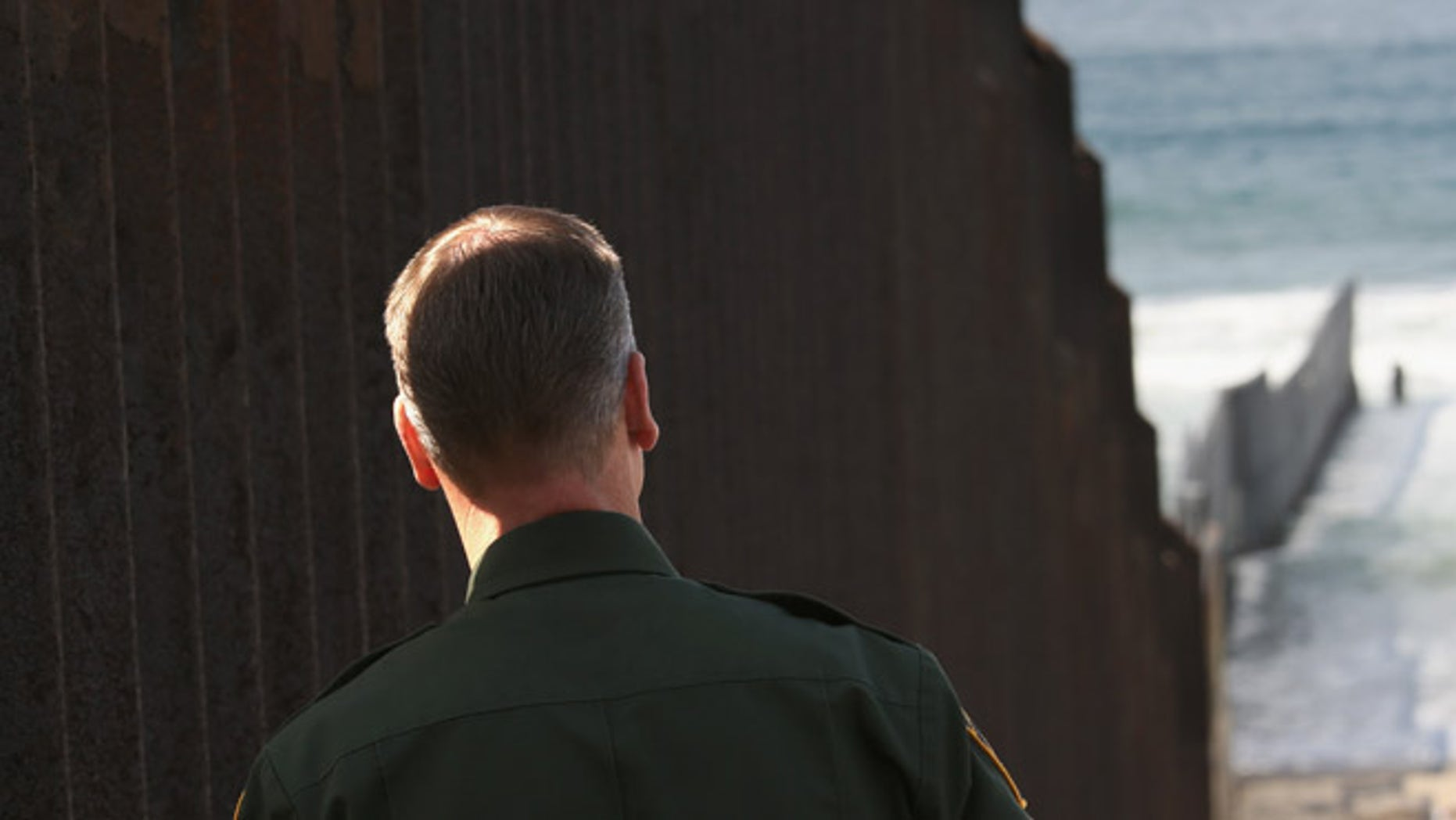 """SAN DIEGO, CA - OCTOBER 03: A U.S. Border Patrol agent looks to where the U.S.-Mexico border fence stretches into the Pacific Ocean on October 3, 2013 in San Diego, California. While hundreds of thousands of government workers were furloughed this week, thousands of Border Patrol agents, air-traffic controllers, prison guards and other federal employees deemed """"essential"""" remain on duty, although their pay may be delayed. (Photo by John Moore/Getty Images)"""