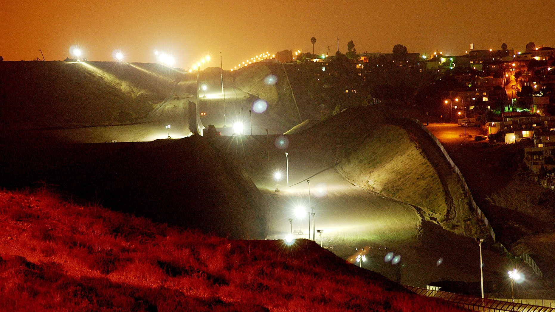 394677 03: Lights, fences, and barren land create an erie no man's land between the Tijuana, Mexico neighborhood of Colonia Libertad (R) and the U.S., September 19, 2001 east of San Ysidro, CA. Operation Gatekeeper's border crackdown of recent years has created the prison-like appearance and has made the border easier to defend against possible terrorist crossings. (Photo by David McNew/Getty Images)