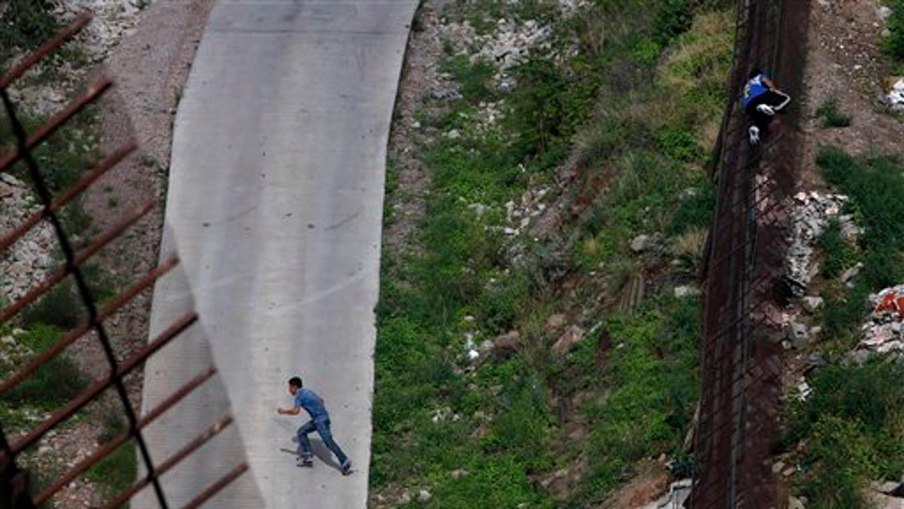 A border fence separating the Arizona-Mexico border.