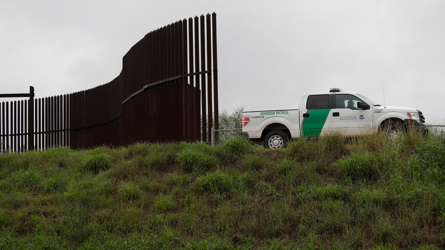 A U.S. Customs and Border Patrol agent passes along a section of border wall in Hidalgo, Texas.