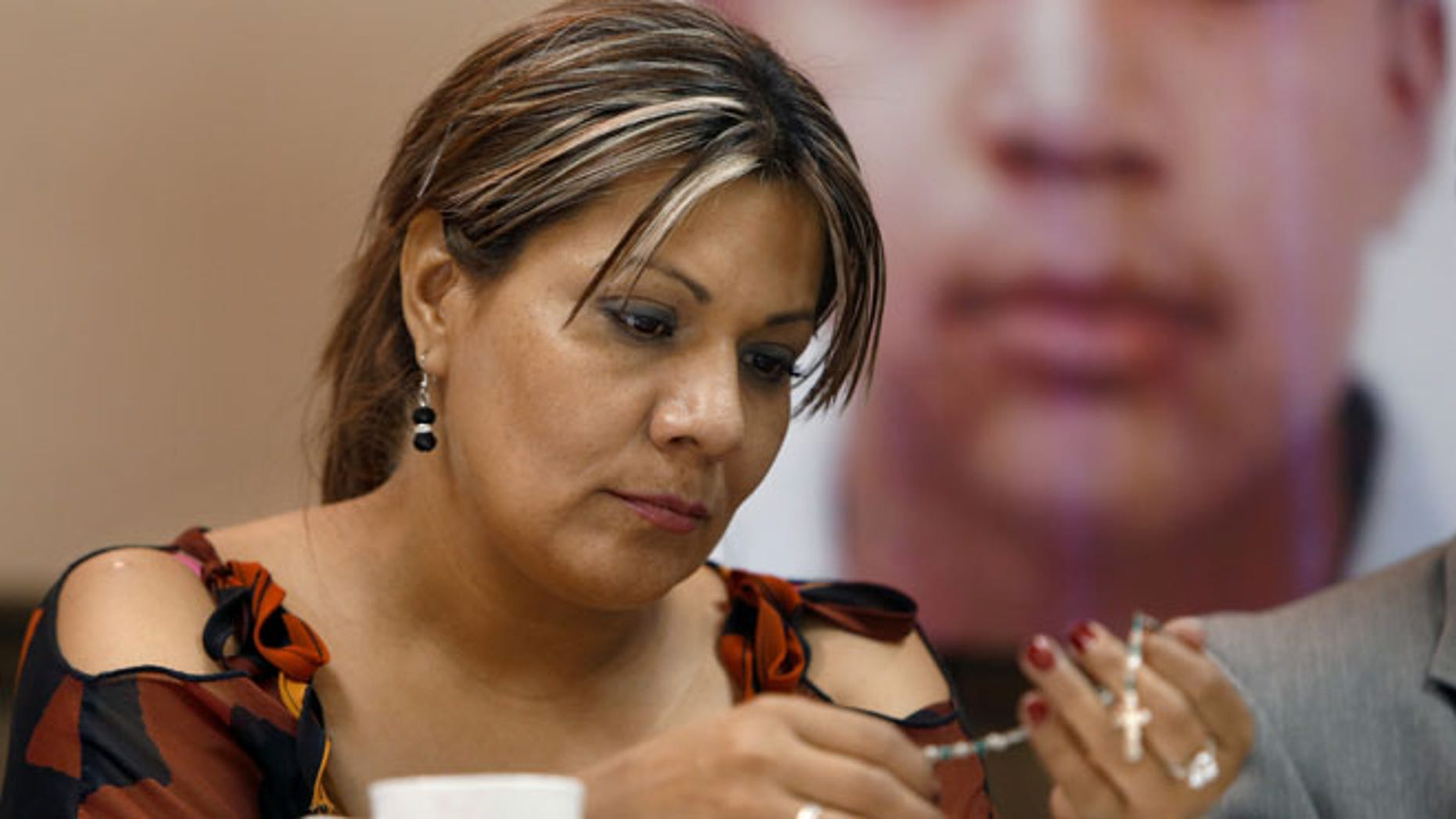 July 29, 2014: Araceli Rodriguez handles a rosary that belonged to her son Jose Antonio Elena Rodriguez, pictured behind her, who was shot and killed by a U.S. Border Patrol agent in October 2012.
