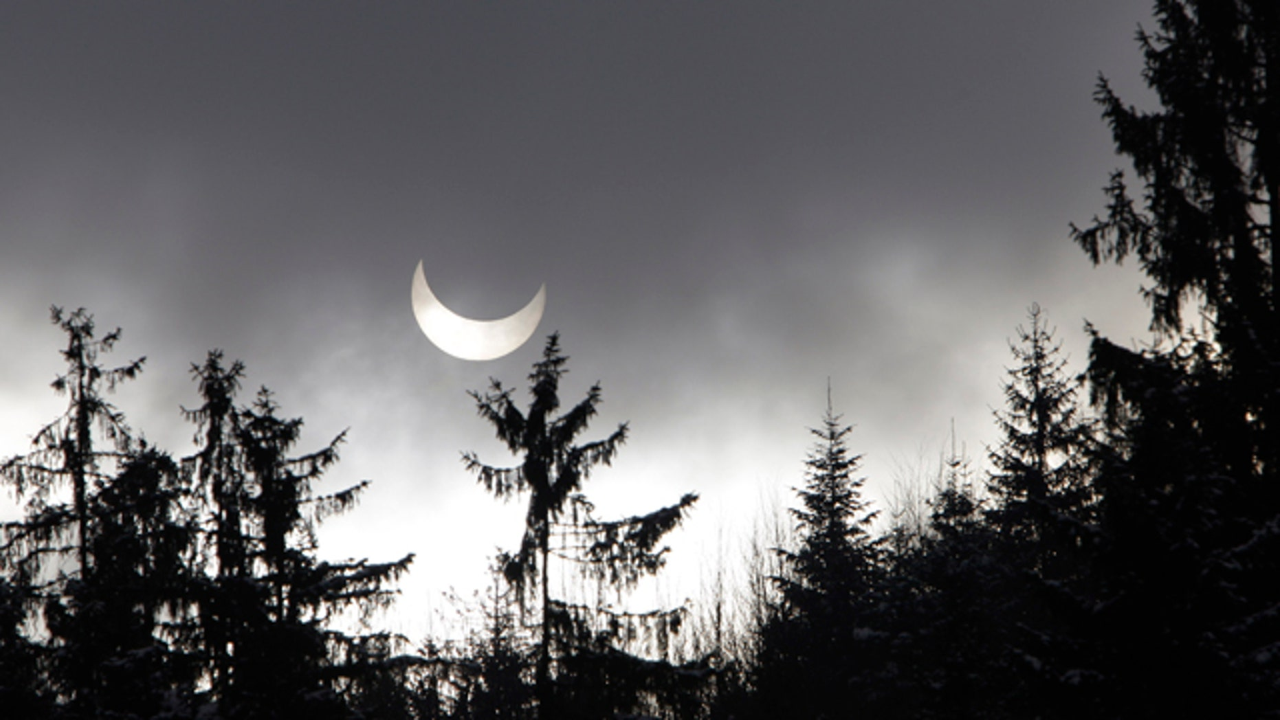A partial solar eclipse is seen through clouds and snow flurries near Sarajevo, Bosnia , on Tuesday, Jan. 4, 2011. A partial solar eclipse began Tuesday in the skies over the Mideast and will extend across much of Europe.