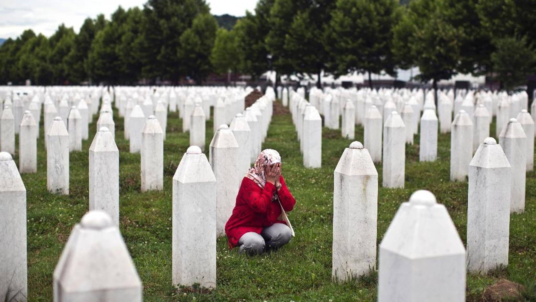 A woman prays next to a grave of her relative at the Potocari memorial complex, in Potocari, close to Srebrenica, 150 kilometers northeast of Sarajevo, Thursday, July 9, 2015. The 20th anniversary of the Srebrenica massacre, the worst crime in Europe after the Nazi era, will be marked on Saturday, July 11, 2015. (AP Photo/Marko Drobnjakovic)