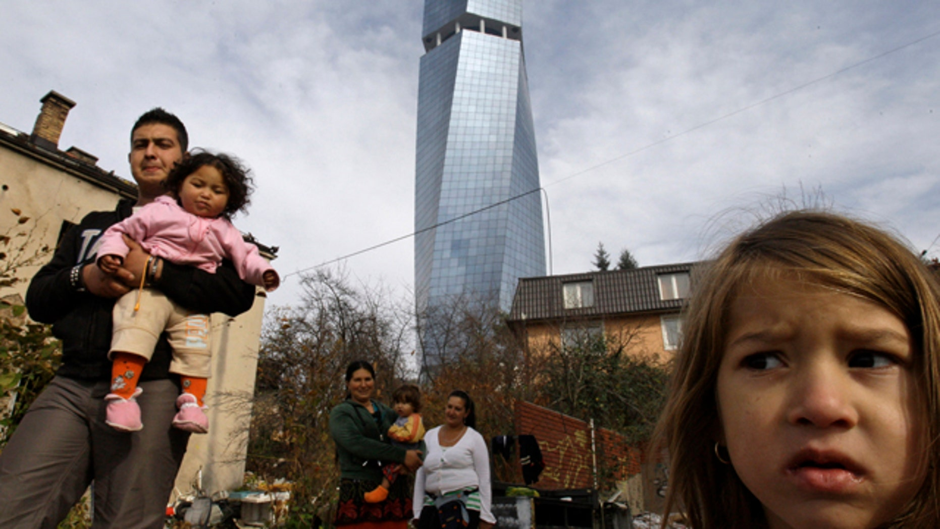 Nov. 12: A Roma family are seen outside their temporary accommodation, backdropped by the largest office block in central Sarajevo, Bosnia.