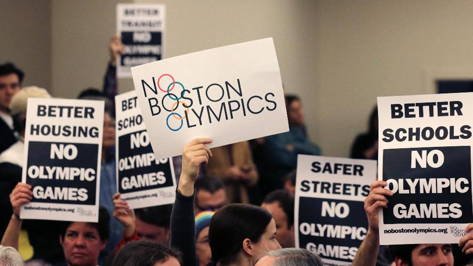 """FILE - In this Feb. 5, 2015, file photo, people hold up placards against the Olympic Games coming to Boston, during the first public forum regarding the city's 2024 Olympic bid, in Boston. Boston's mayor delivered a harsh blow to the city's effort to host the 2024 Olympics on Monday, July 27, 2015,  when he declared he wouldn't sign any document """"that puts one dollar of taxpayer money on the line for one penny of overruns on the Olympics.""""  That document is the host city contract that most in the Olympics consider crucial to any city's success.  (AP Photo/Charles Krupa, File)"""