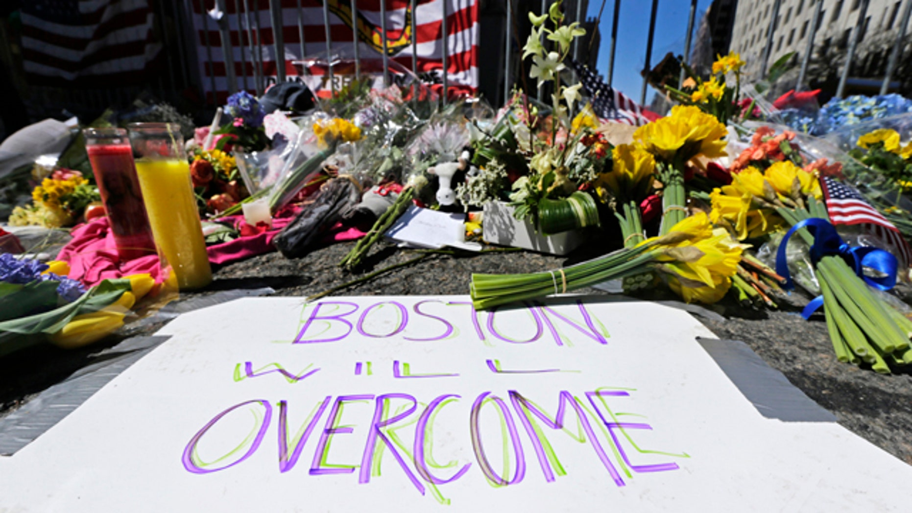 FILE  - In this April 17, 2013 photograph, flowers and signs adorn a barrier at Boylston Street near the of finish line of the Boston Marathon at a makeshift memorial for victims and survivors of the bombing. Boston will mark the second anniversary of the 2013 marathon bombings Wednesday with a subdued remembrance that includes a moment of silence, the pealing of church bells and a call for kindness. (AP Photo/Charles Krupa, File)