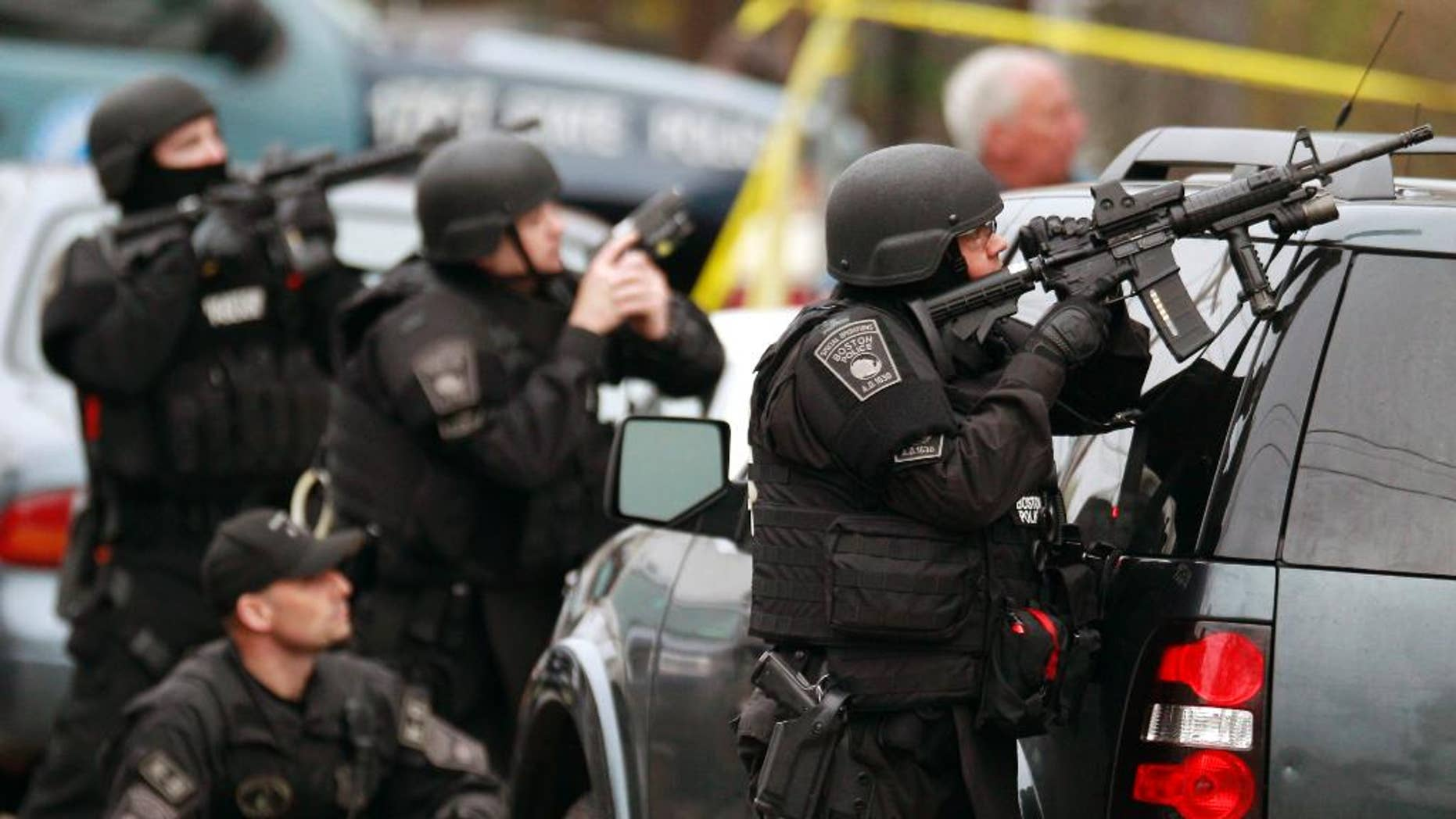 FILE - In this April 19, 2013 file photo, police in tactical gear surround an apartment building while looking for a suspect in the Boston Marathon bombings in Watertown, Mass. A Harvard University report released Thursday, April 3, 2014, on the response to the bombings was largely positive, but criticized law enforcement for the chaotic gunfight in which one suspect was killed and a police officer seriously injured, because it lacked coordination.  (AP Photo/Charles Krupa, File)