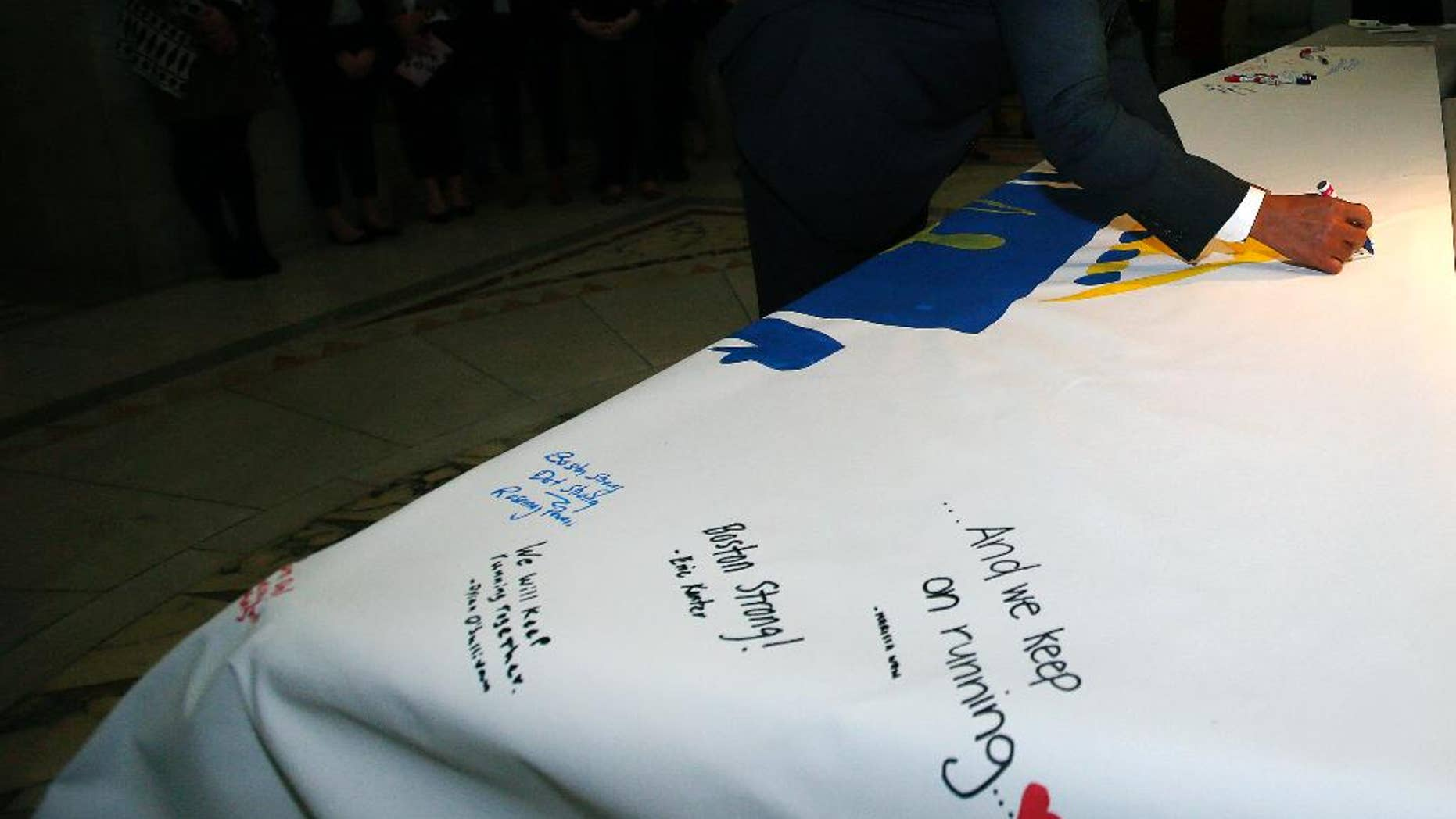 Mass. Gov. Deval Patrick signs the America 4 Prayer Canvas in support and remembrance of the 2013 Boston Marathon bombing victims and survivors at the Statehouse in Boston, Friday, April 11, 2014. (AP Photo/Elise Amendola)