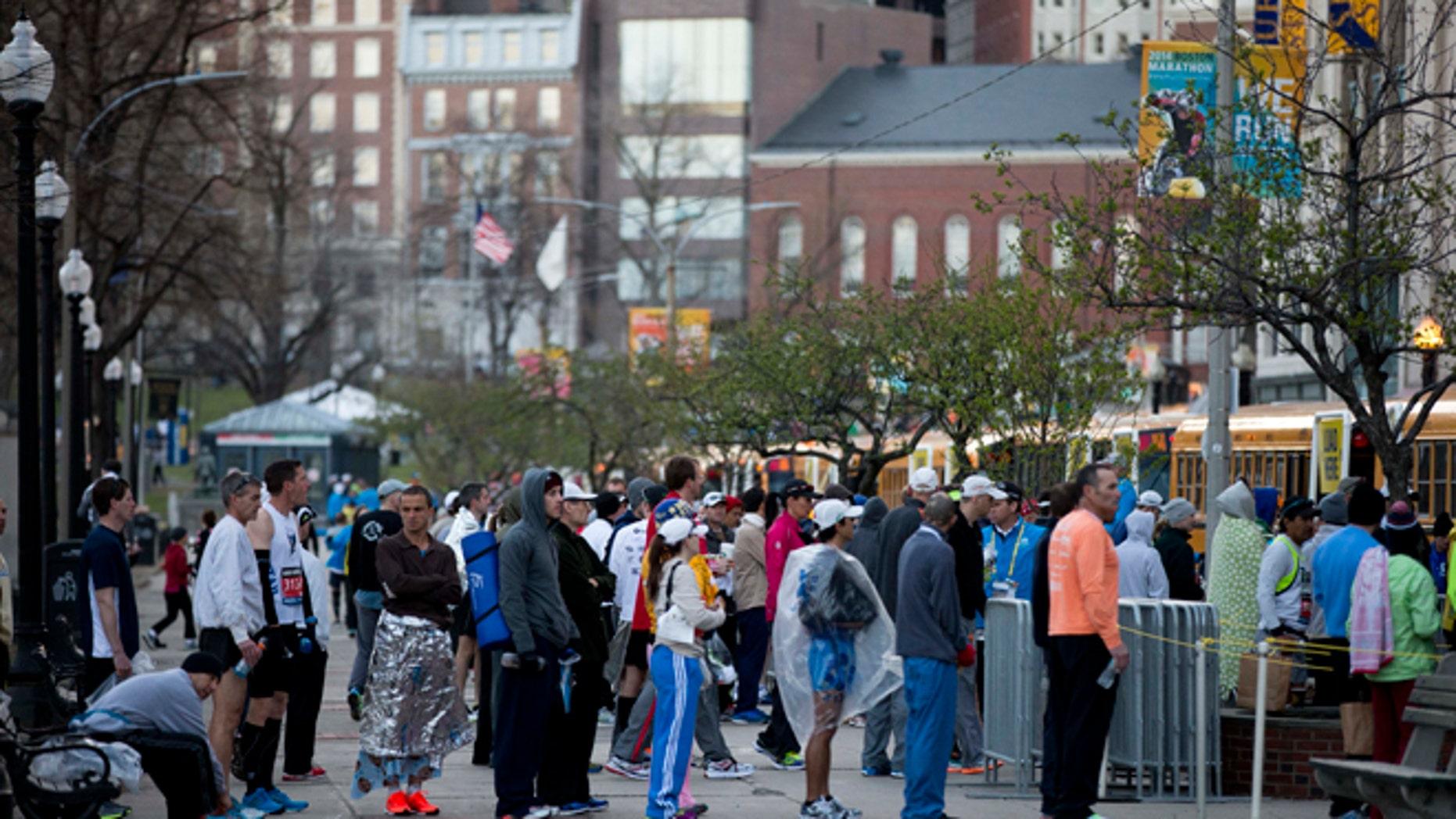 Runners cue to board busses ahead of the 118th Boston Marathon Monday, April 21, 2014 in Boston. (AP Photo/Matt Rourke)
